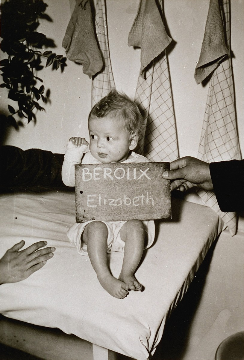 Elizabeth Beroux with a name card intended to help any of her surviving family members locate her at the Kloster Indersdorf DP camp.  This photograph was published in newspapers to facilitate reuniting the family.