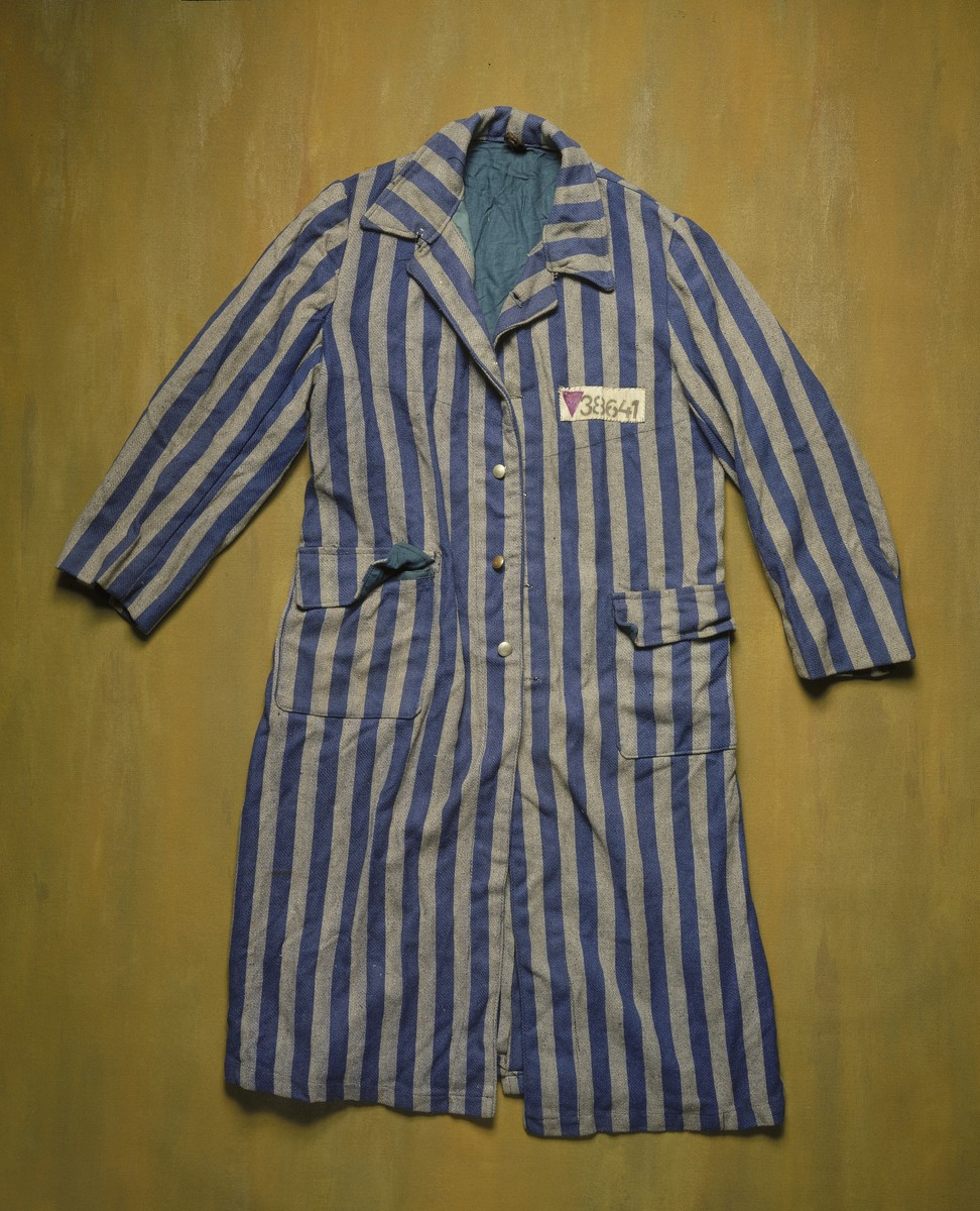The striped overcoat of a prison uniform worn at the Buchenwald concentration camp bearing a purple triangle on the number patch.  The prisoner number is #38641.  The inverted purple triangle badge identifies the prisoner as a Jehovah's Witness.
