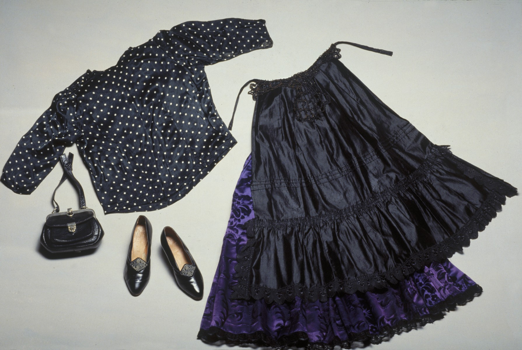 Composite photograph of items of apparel used by female members of a German Sinti (Gypsy) tribe, including two skirts, a blouse, a purse and a pair of shoes.