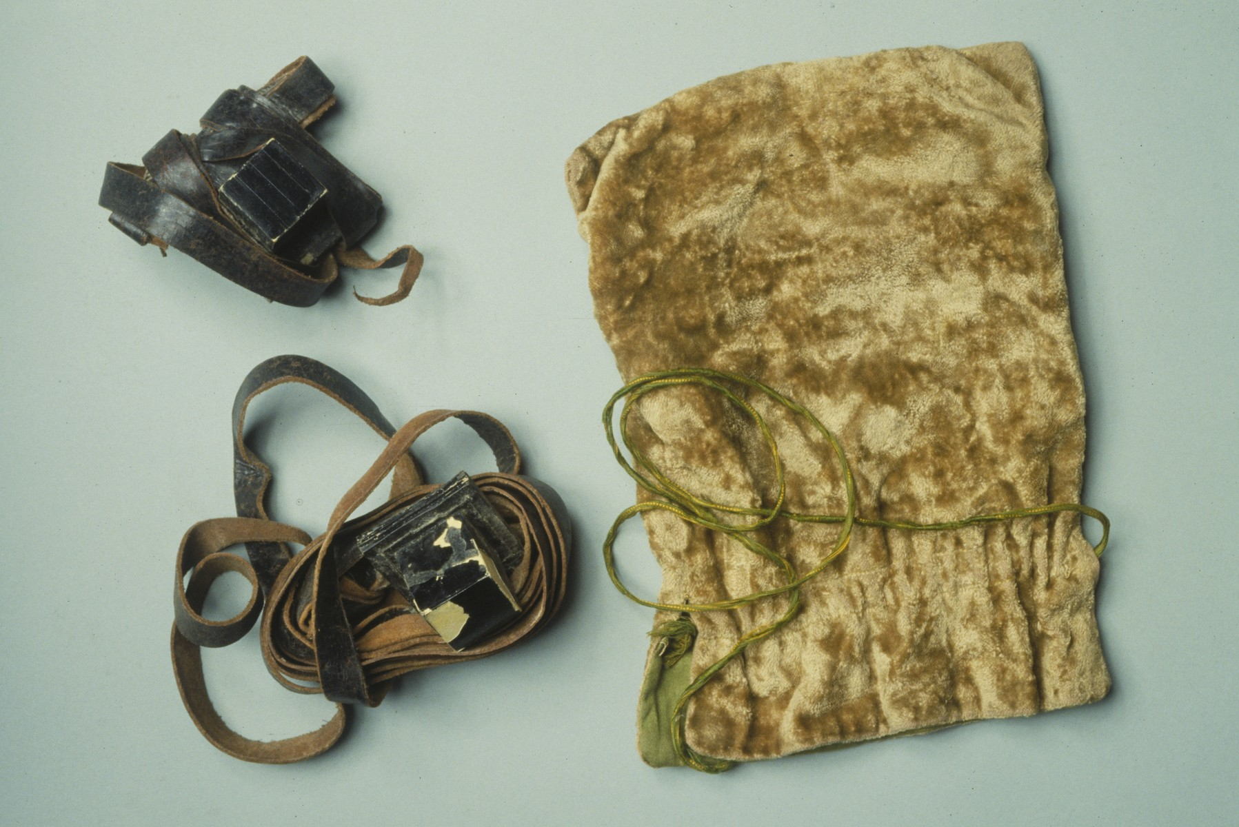 A set of Jewish ritual phylacteries (tefillin) and a gold velour tefillin bag originally owned by Rabbi Ferenc Hevesi.