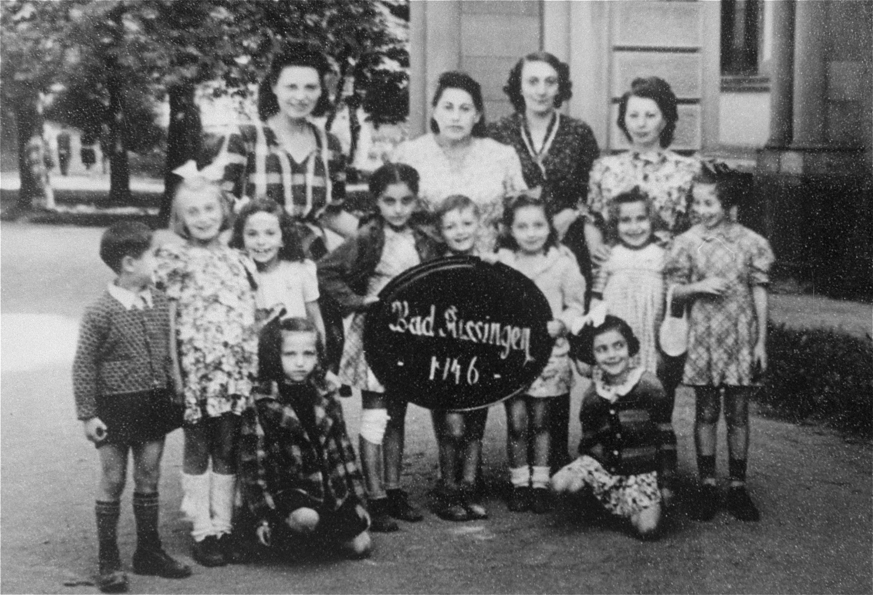 Group portrait of Jewish DP women and children at the Bad Kissingen displaced persons camp.  The children survived the war in hiding.  Among those pictured is Esther Zelowicz (now Edith Cove) standing in the back row, first on the left.