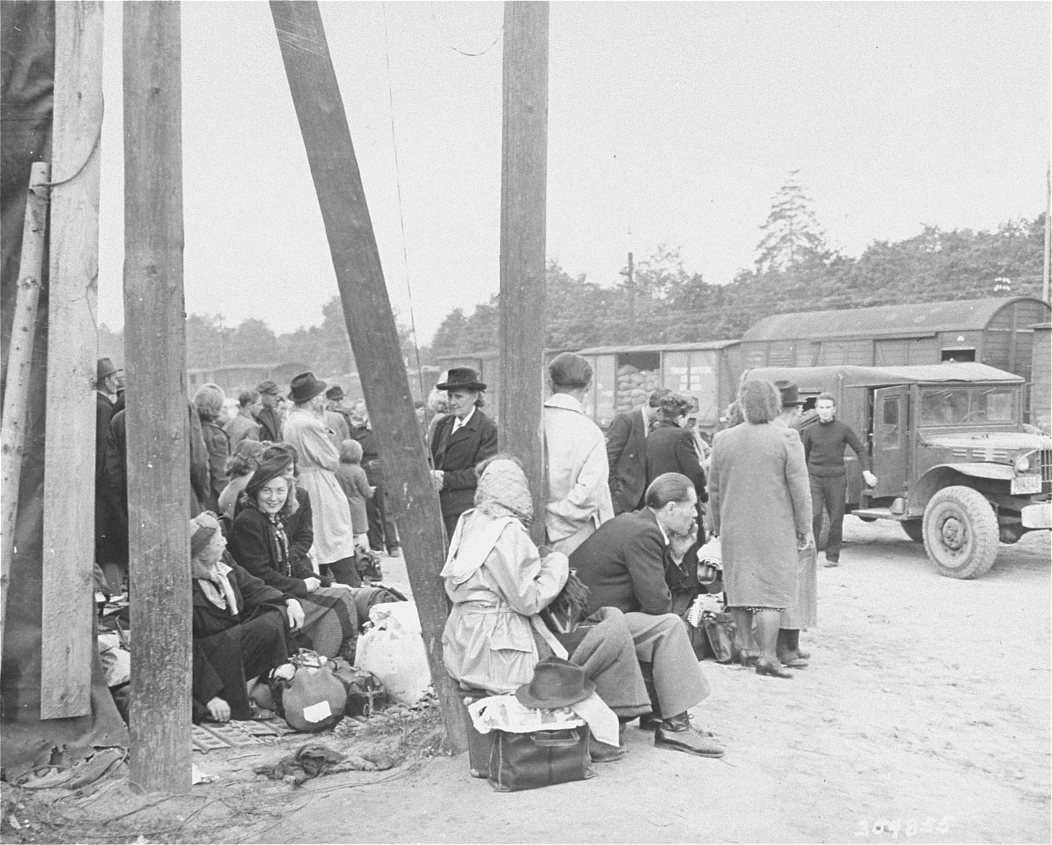 """Jewish DPs who have been evacuated from Berlin to Frankfurt as a result of the Soviet blockade, wait at the Rhine Main Airfield for transport to displaced persons camps.  The original caption reads, """"Jewish displaced persons arrive by plane at the Rhine Main Airfield, Frankfurt, Germany, from the blockaded city of Berlin, on operation """"Vittles"""". 150 came in the first group, and 180 are expected to arrive on July 24, 1948. Most of these DPs have been granted visas by the new State of Israel, and will go to DP camps in the U.S. zone to await shipment to Palestine, while others will leave for Canada, France and the U.S.. Here DPs wait for trucks to arrive to carry them to trains."""""""