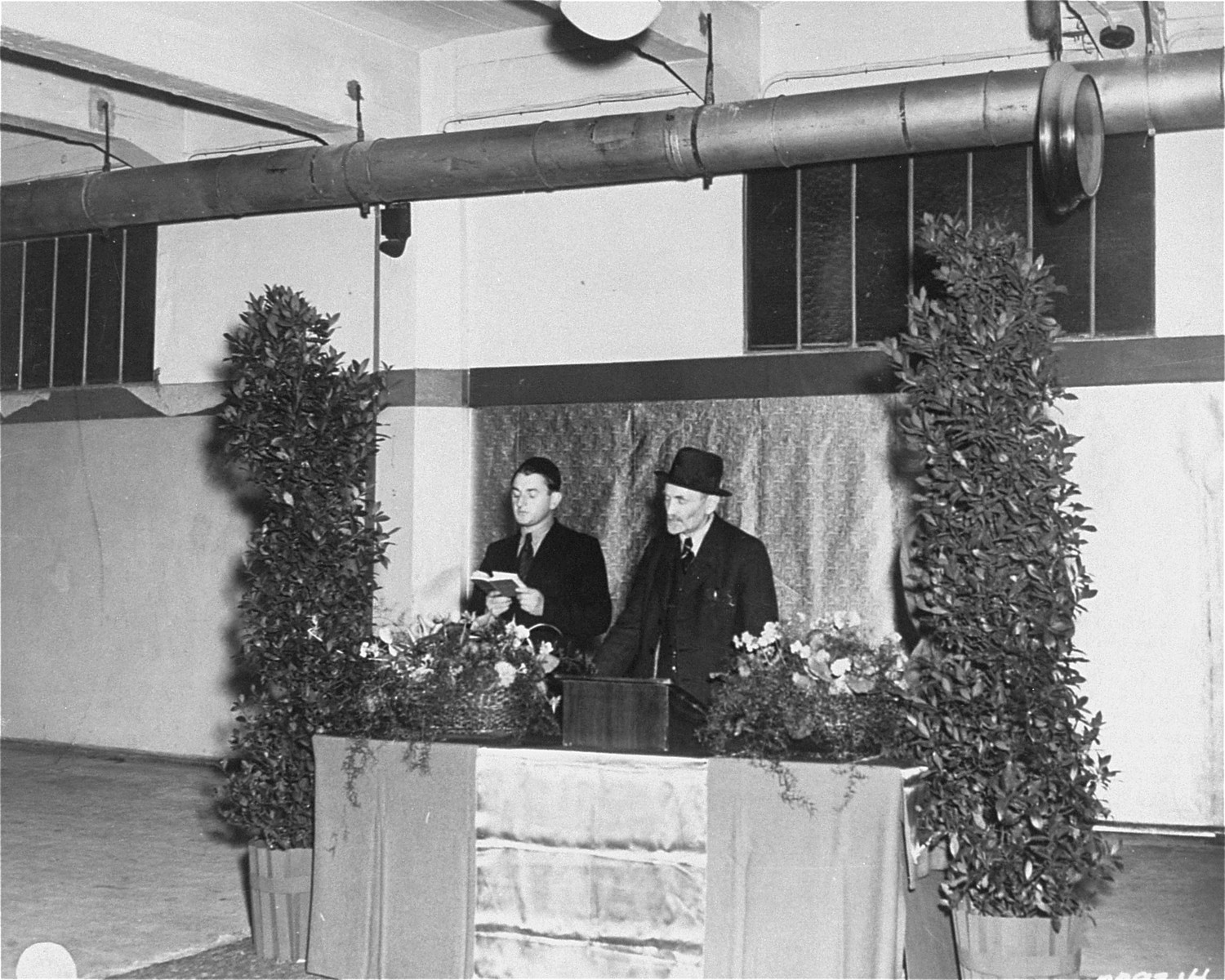 Rabbi Samuel Snieg (right), head of the Central Committee of Liberated Jews, stands at the podium during  opening ceremonies for the first Jewish bakery in Berlin since the end of the Nazi period.