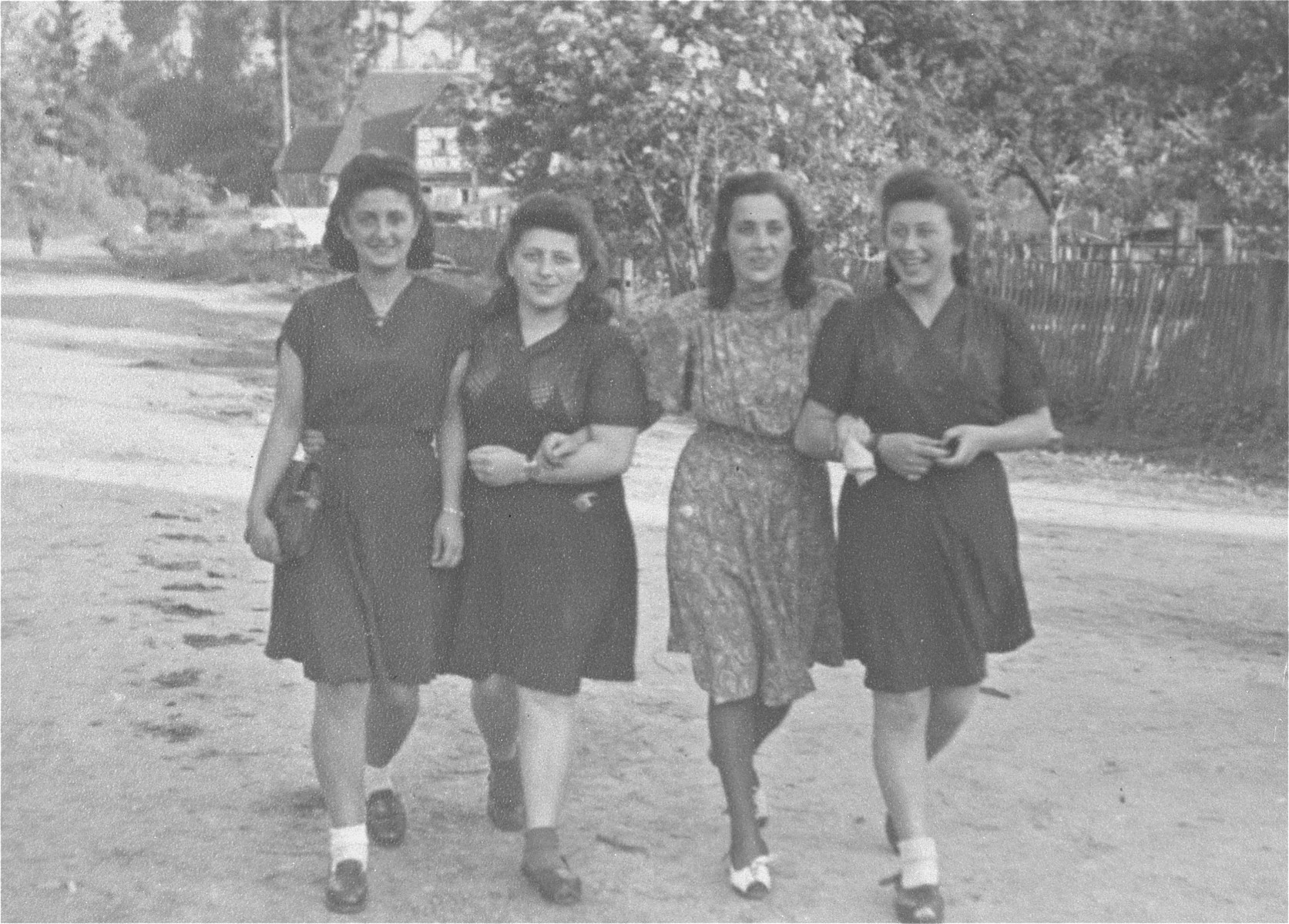 Four young Jewish women who were recently liberated from the Schatzlar labor camp, walk arm-in-arm along a road.  Pictured from left to right are: unknown, Herscovicz (from Sosnowiec), Gusta Fiszgrund (from Crzanow), and Pola Herscovicz (from Sosnowiec).