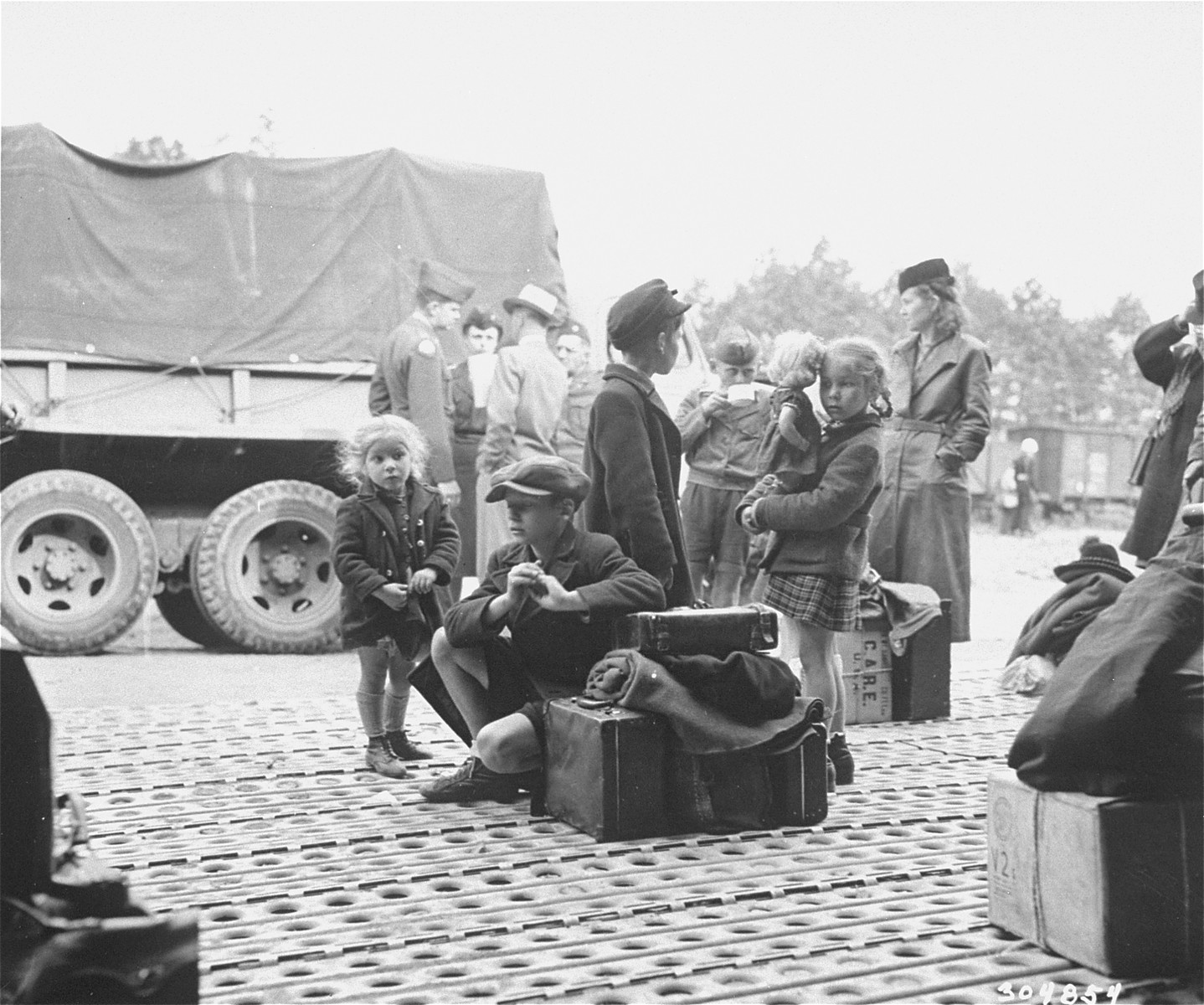 "Jewish DPs who have been evacuated from Berlin to Frankfurt as a result of the Soviet blockade, wait at the Rhine Main Airfield for transport to displaced persons camps.  The original caption reads, ""Jewish displaced persons arrive by plane at the Rhine Main Airfield, Frankfurt, Germany, from the blockaded city of Berlin, on operation ""Vittles"".  150 came in the first group, and 180 are expected to arrive on July 24, 1948. Most of these DPs have been granted visas by the new State of Israel, and will go to DP camps in the U.S. zone to await shipment to Palestine, while others will leave for Canada, France and the U.S.. Here DPs wait for trucks to arrive to carry them to trains."""