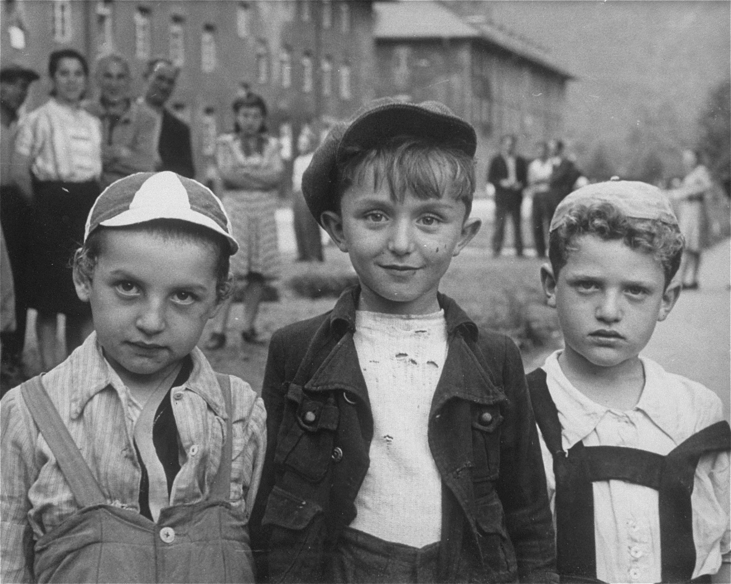 Portrait of three young Jewish boys wearing camps standing outside in the Bad Reichenhall displaced persons camp.