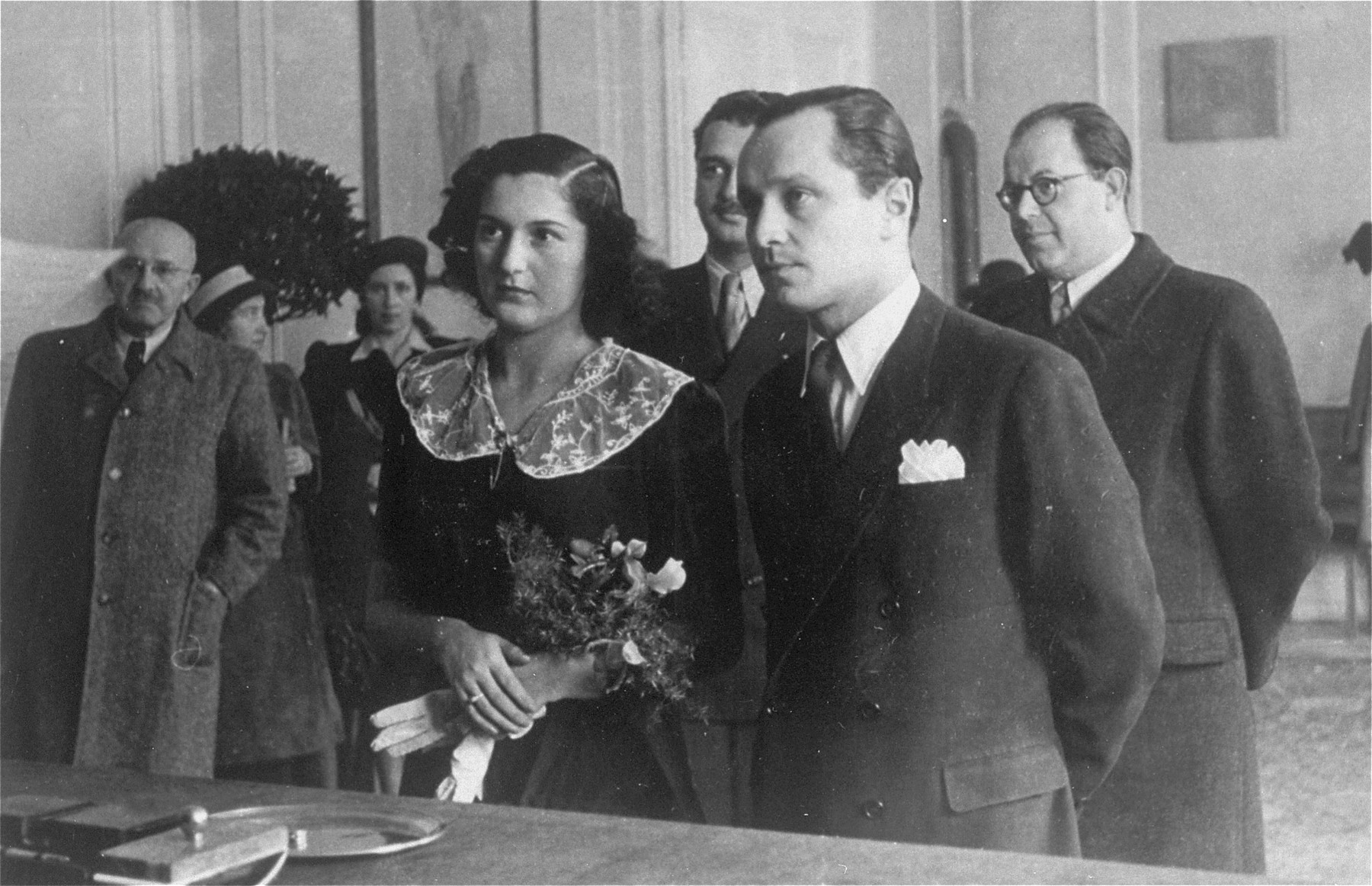 The marriage of Czech-Jewish survivors Frantisek Kohn and Gertie Gans before a judge at the city hall in Prague.    Among those pictured are: Viktor Kohn, who came from Palestine (at the left with his hand in his pocket); Yarmila Guth (behind Viktor, wearing a hat); Zdenka Neuman (next to Yarmila ); Otto Gans Gregor (Gertie's brother, standing behind the couple, with a mustache); and Dr. Guth (at the right, wearing glasses).