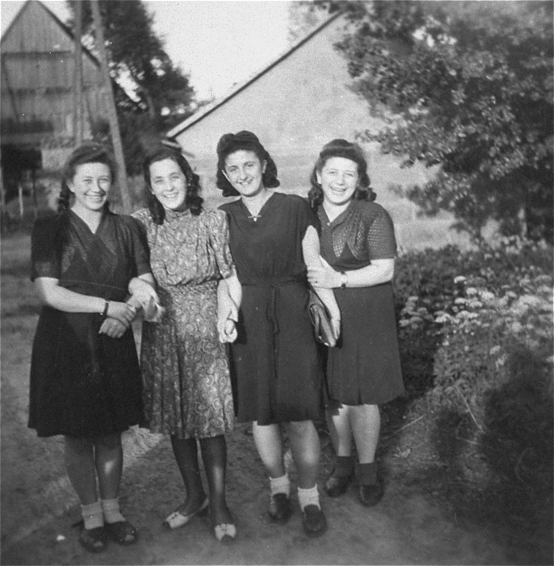 Four young Jewish women who were recently liberated from the Schatzlar labor camp, pose outside in front of a group of buildings.  Pictured from left to right are:  Pola Herscovicz (from Sosnowiec), Gusta Fiszgrund (from Crzanow), unknown, and Herscovicz (from Sosnowiec).