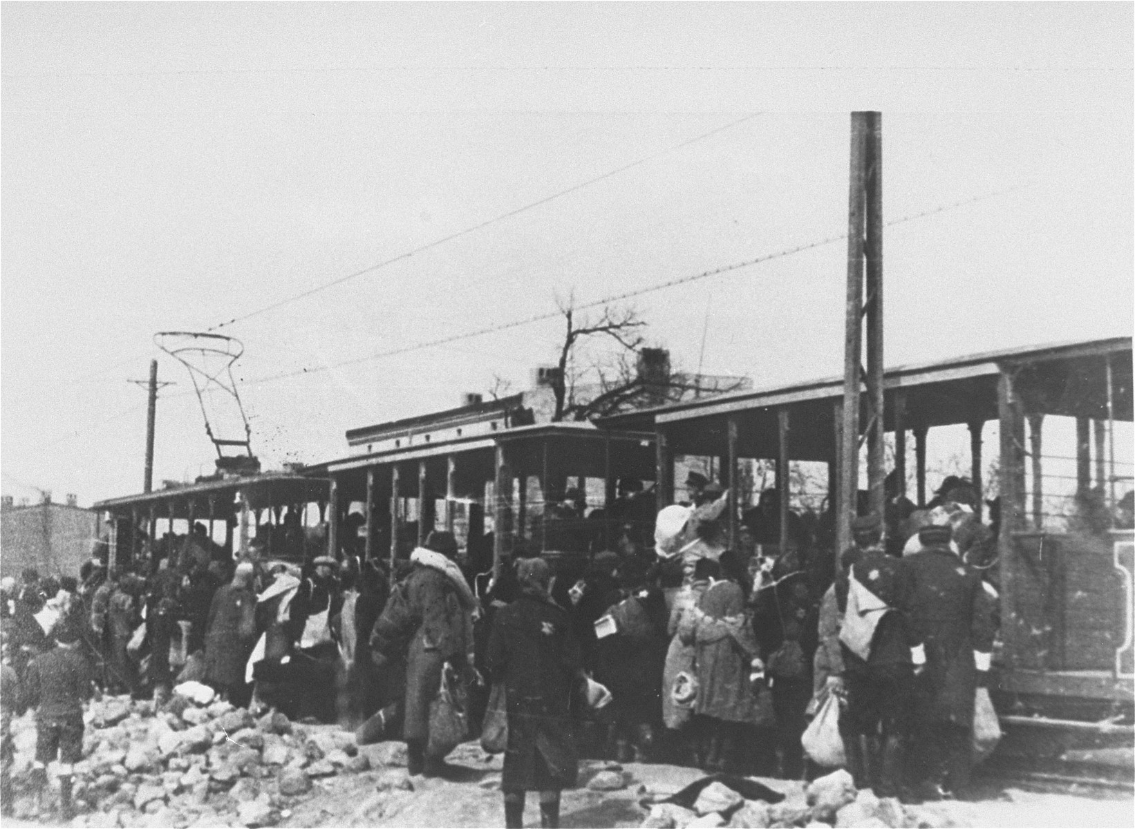 Newly arrived Jews, probably from Central Europe, board streetcars that will take them into the ghetto.
