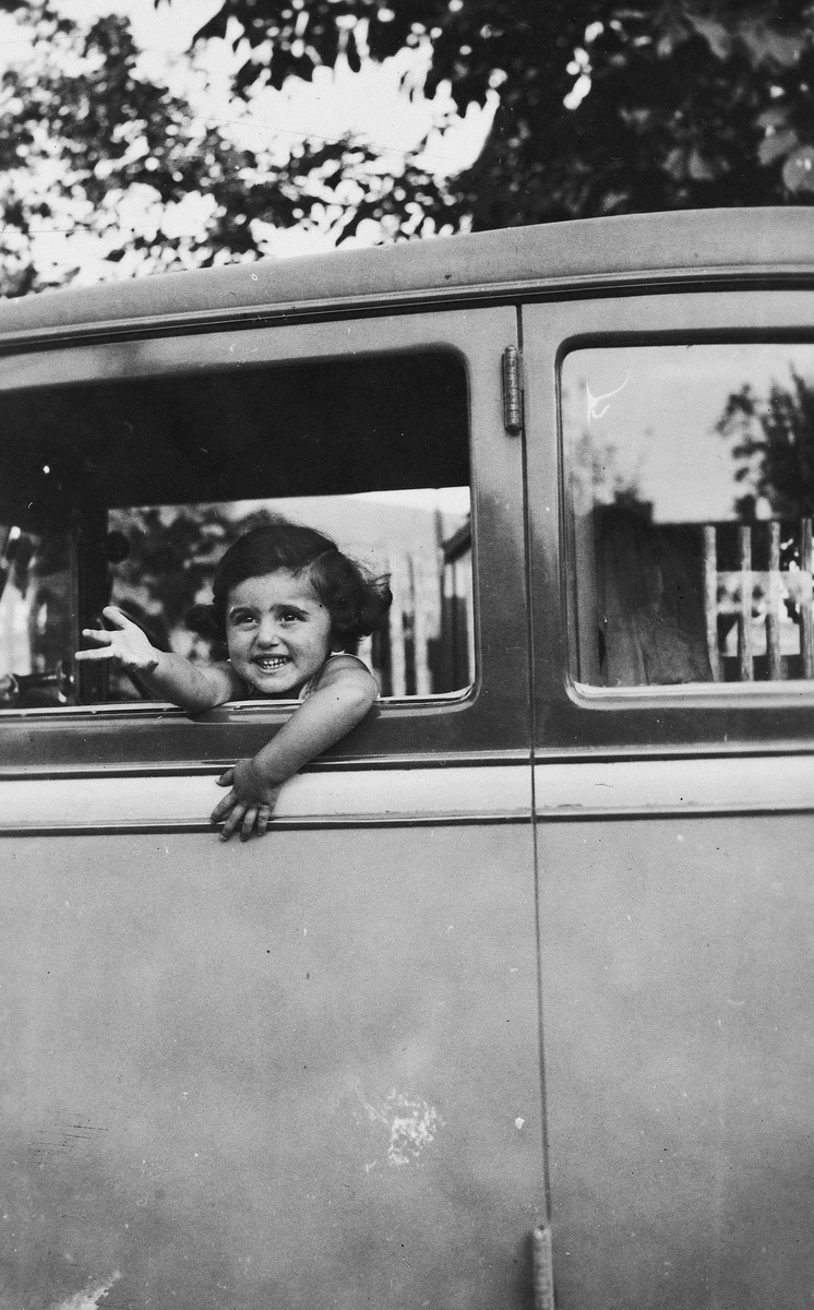 Kitty Weichherz leans out the window of an automobile.  This photo was taken from the diary of Kitty's life written by her father, Bela Weichherz.