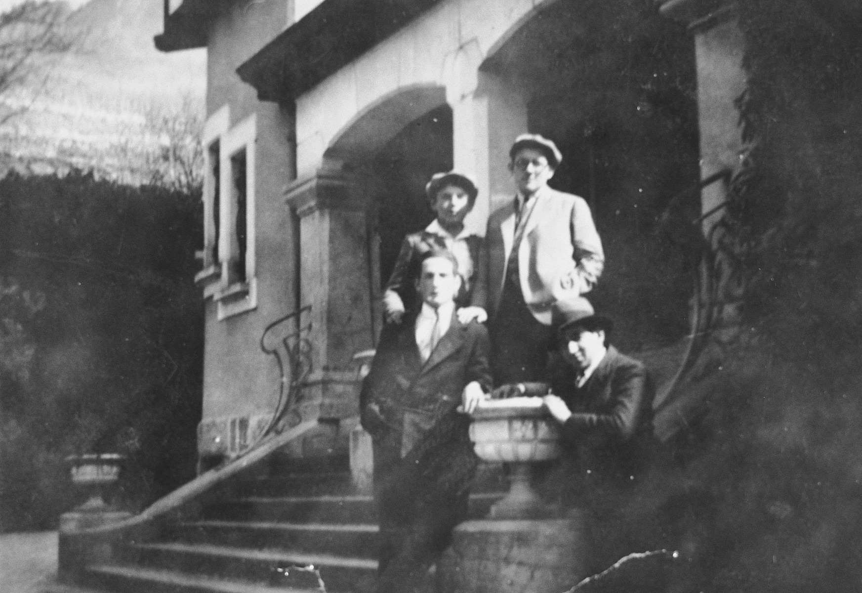 Four young men pose on the steps outside their yeshiva.