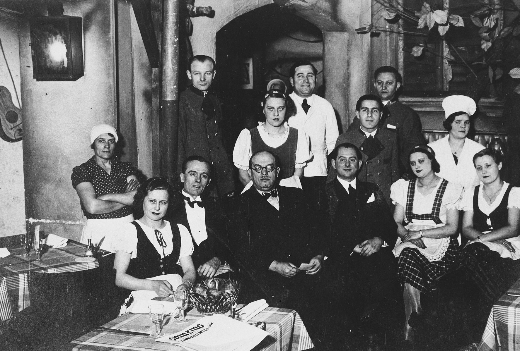 The staff of a kosher boarding home poses together in the dining room.  Ignatz Frankel is in the center wearing a bow tie and glasses.