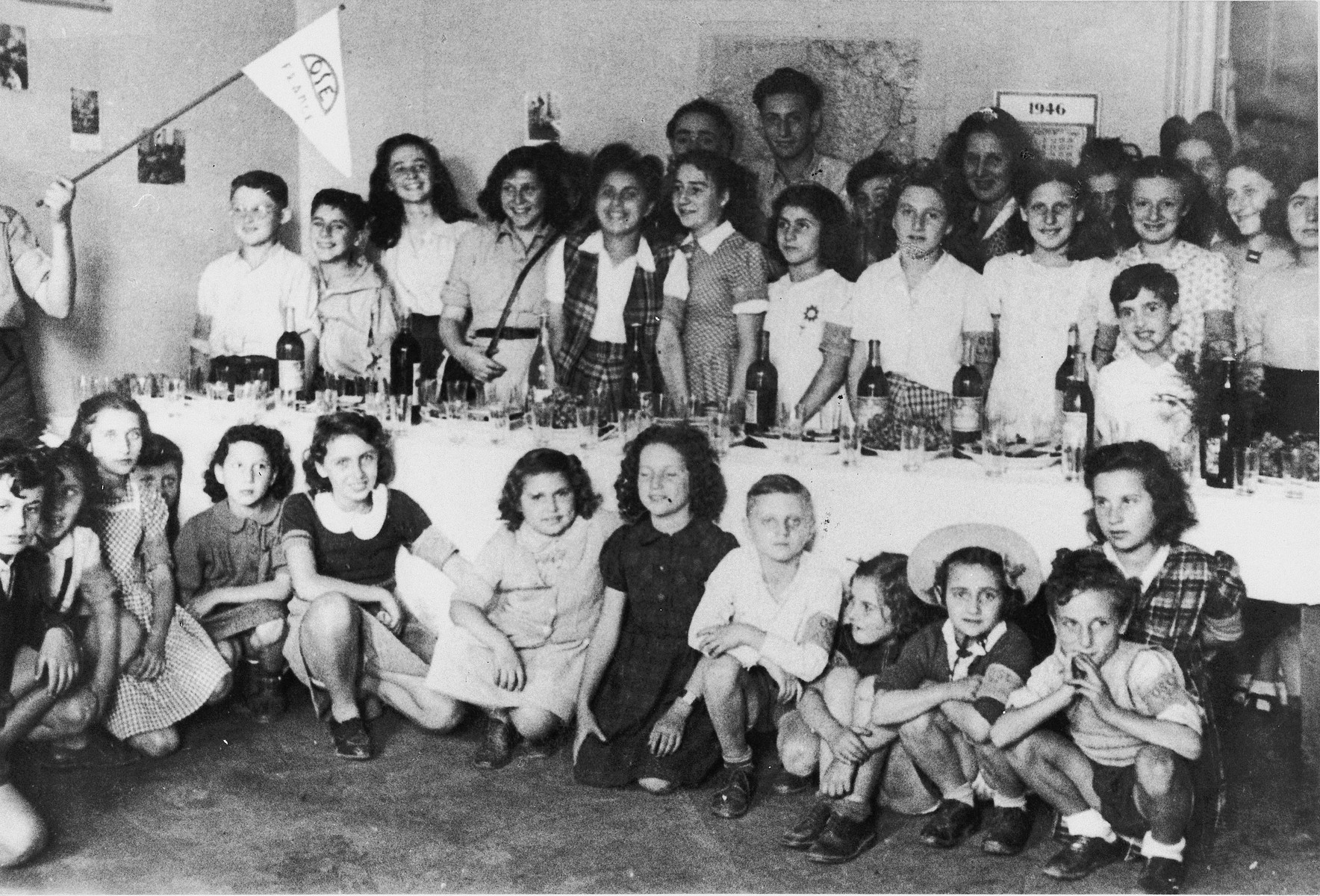Children gather around a festive table set with wine and wine cups in an OSE home in France.  Among those pictured is former St. Louis passenger, Judith Koeppel.