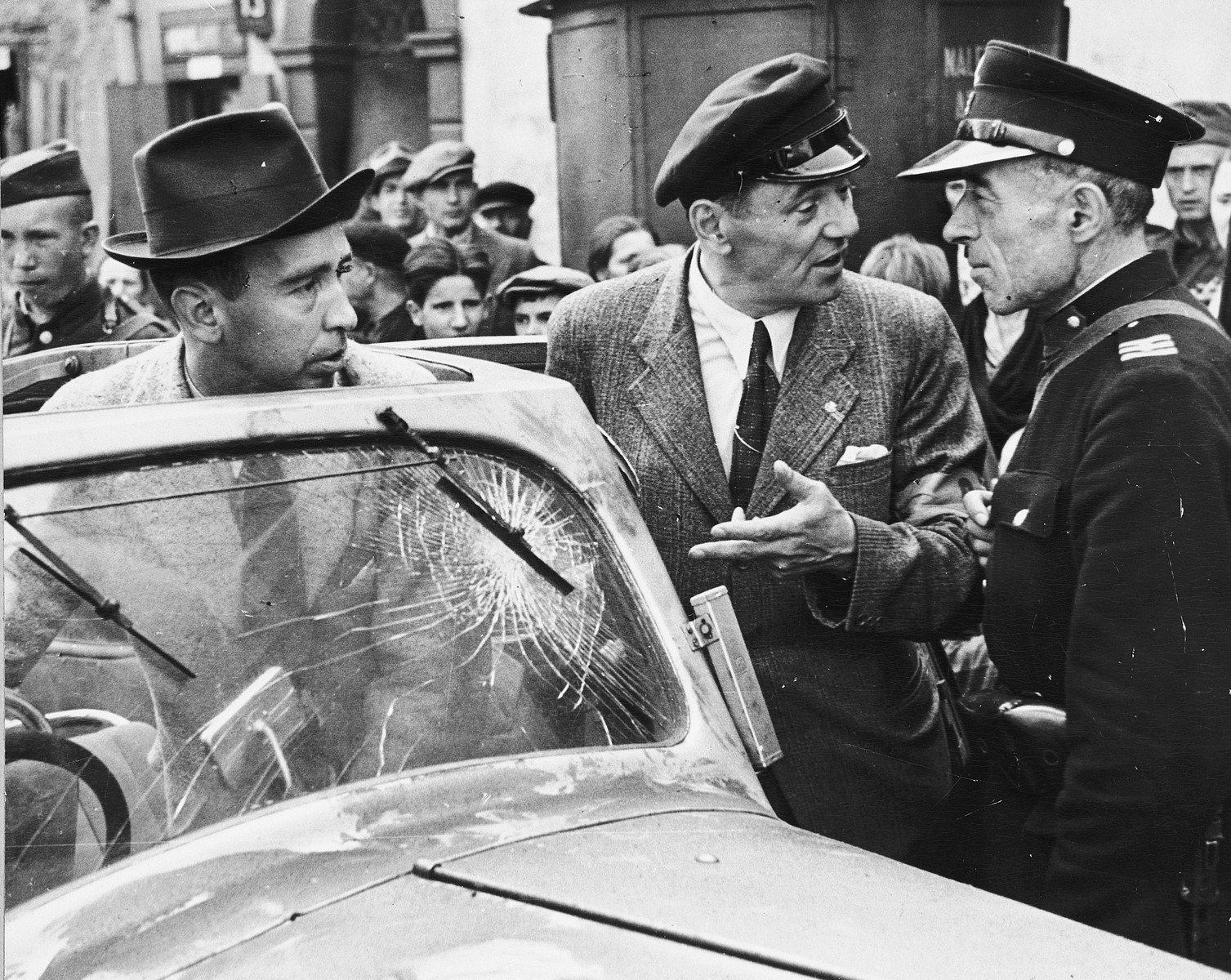 A crowd of Polish civilians watches as Julien Bryan's interpreter explains to a policeman that the man in the turned-up fedora is American photographer, Julien Bryan and not a German spy.