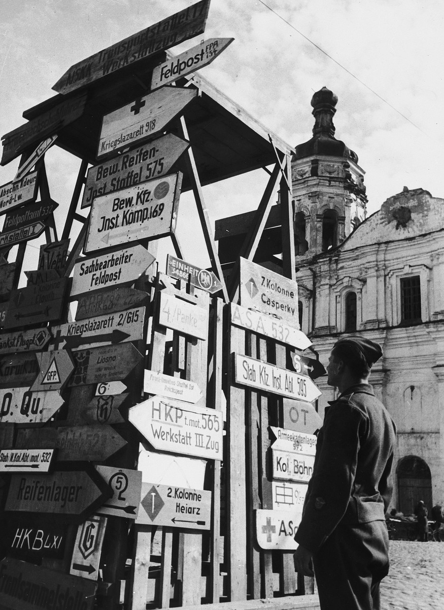 A German soldier examines directional arrow signs attached to a wooden fence.