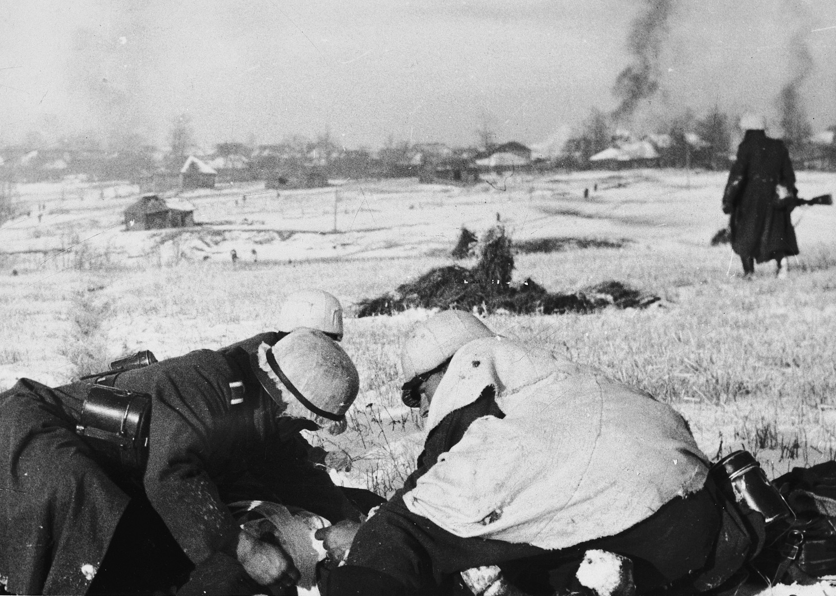 Three German soldiers inspect a document in a snowy field while another views a burning village in the distance [probably in the Soviet Union].