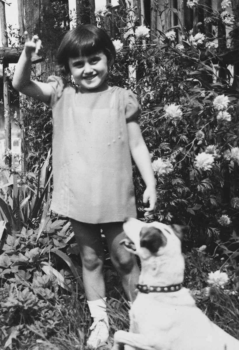 Kitty Weichherz plays with a dog in a garden.  This photo was taken from the diary of Kitty's life written by her father, Bela Weichherz.