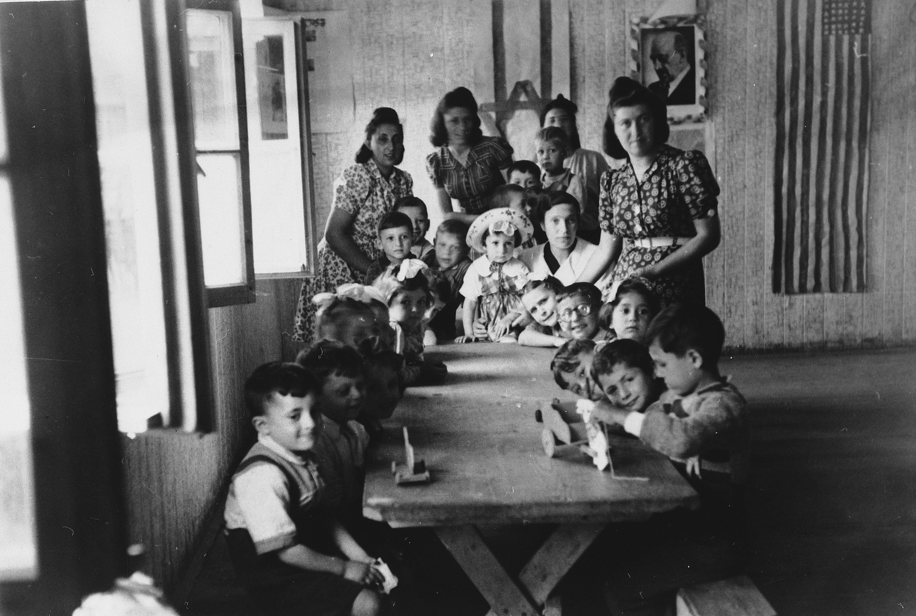 Preschool children and their teachers pose around a long table in the Wels DP camp.