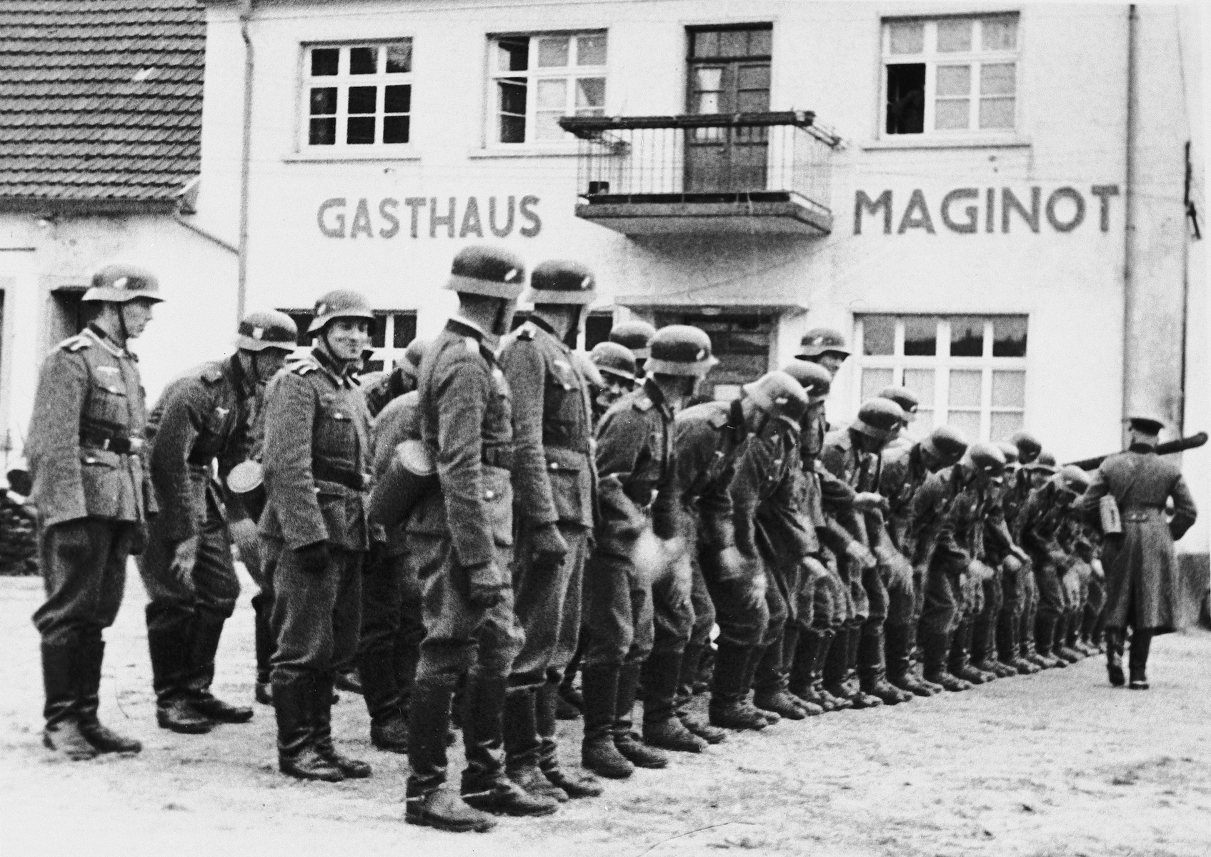 A German officer inspects his troops in front of the Gasthaus Maginot in Eppenbrunn, Germany.