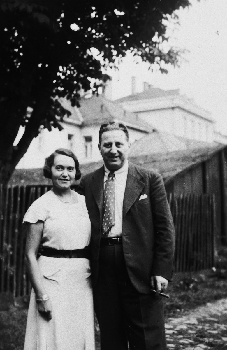 A Jewish couple pose on a garden path next to a fence.  Pictured are Esti and Bela Weichherz.  This photo was taken from the diary of Kitty's life written by her father, Bela Weichherz.