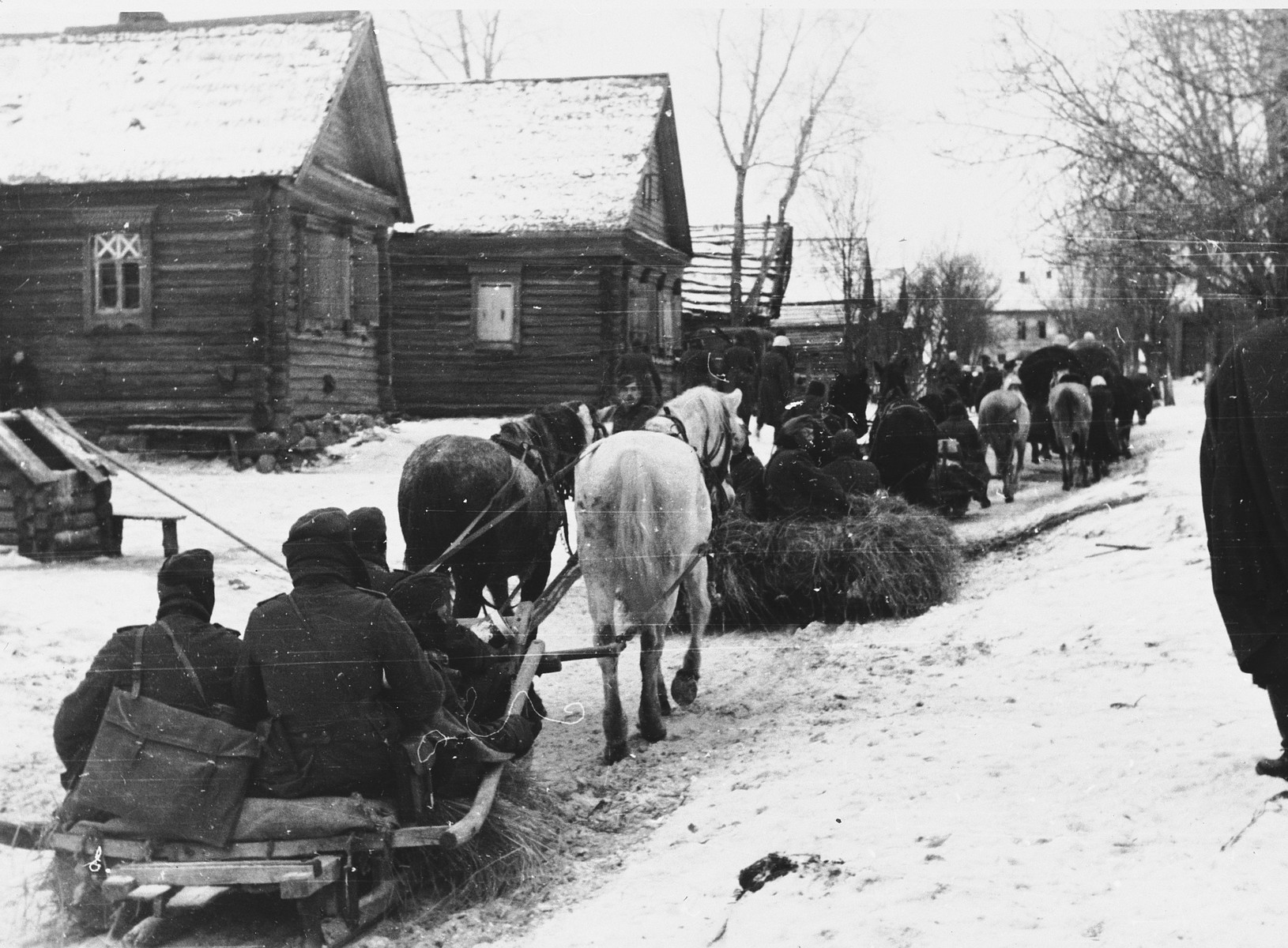German soldiers ride in a caravan of horse-drawn sleighs past wooden homes in a village [probably in the Soviet Union].