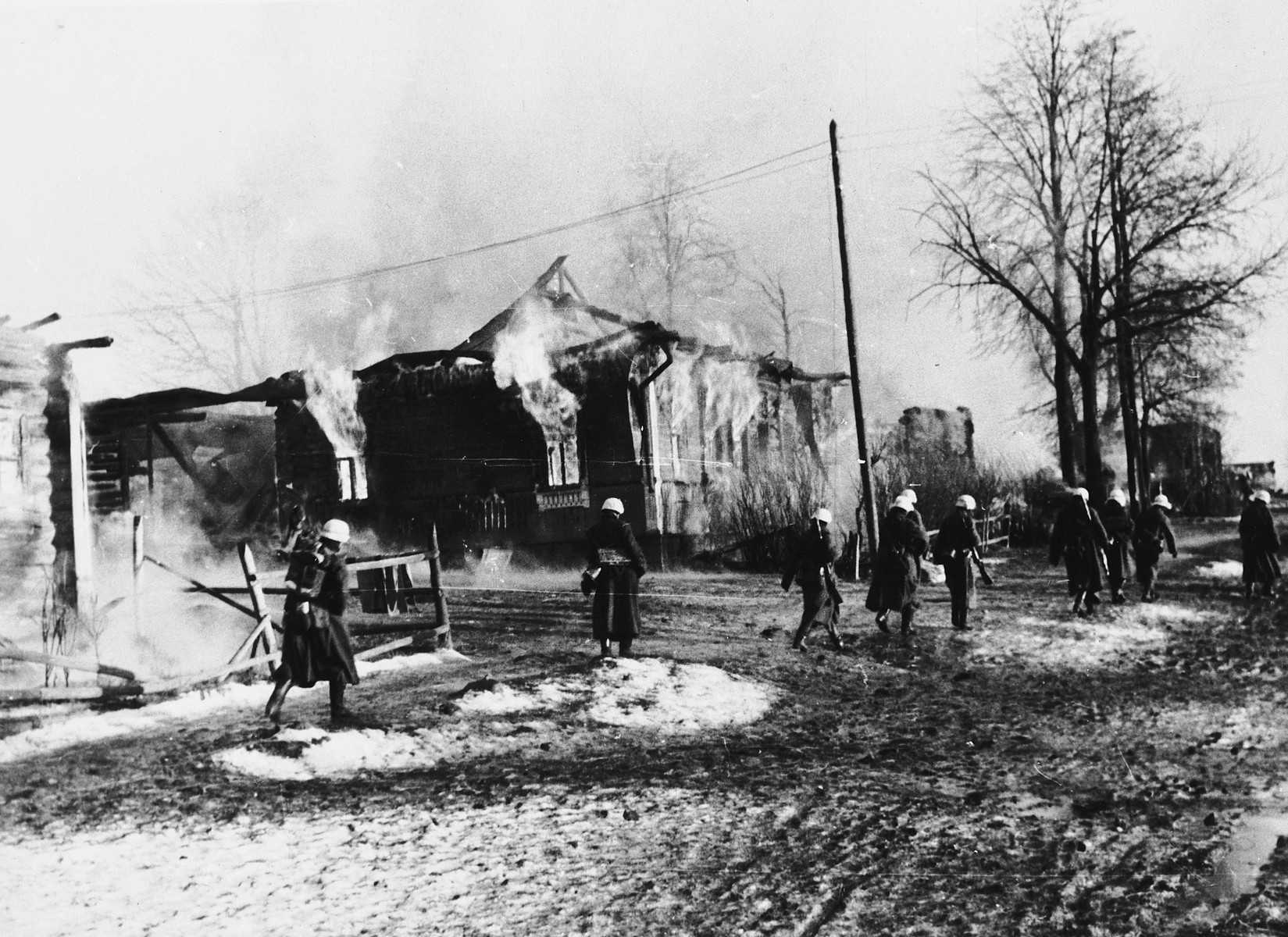 German soldiers carrying weapons walk down a street of a burning village [probably in the Soviet Union].