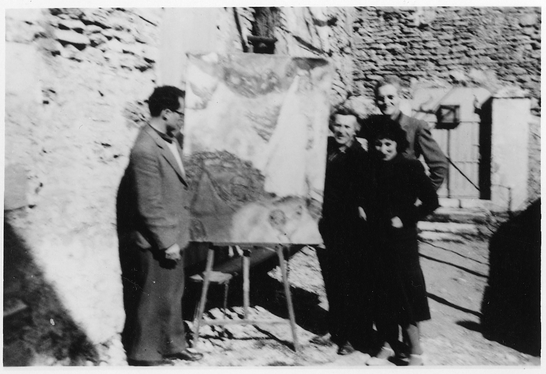 Varian Fry (left) views a Chagall painting outside the artist's home in Gordes.  Pictured from left to right are Varian Fry, Marc Chagall, Bella Chagall, and Hiram Bingham (behind Bella).
