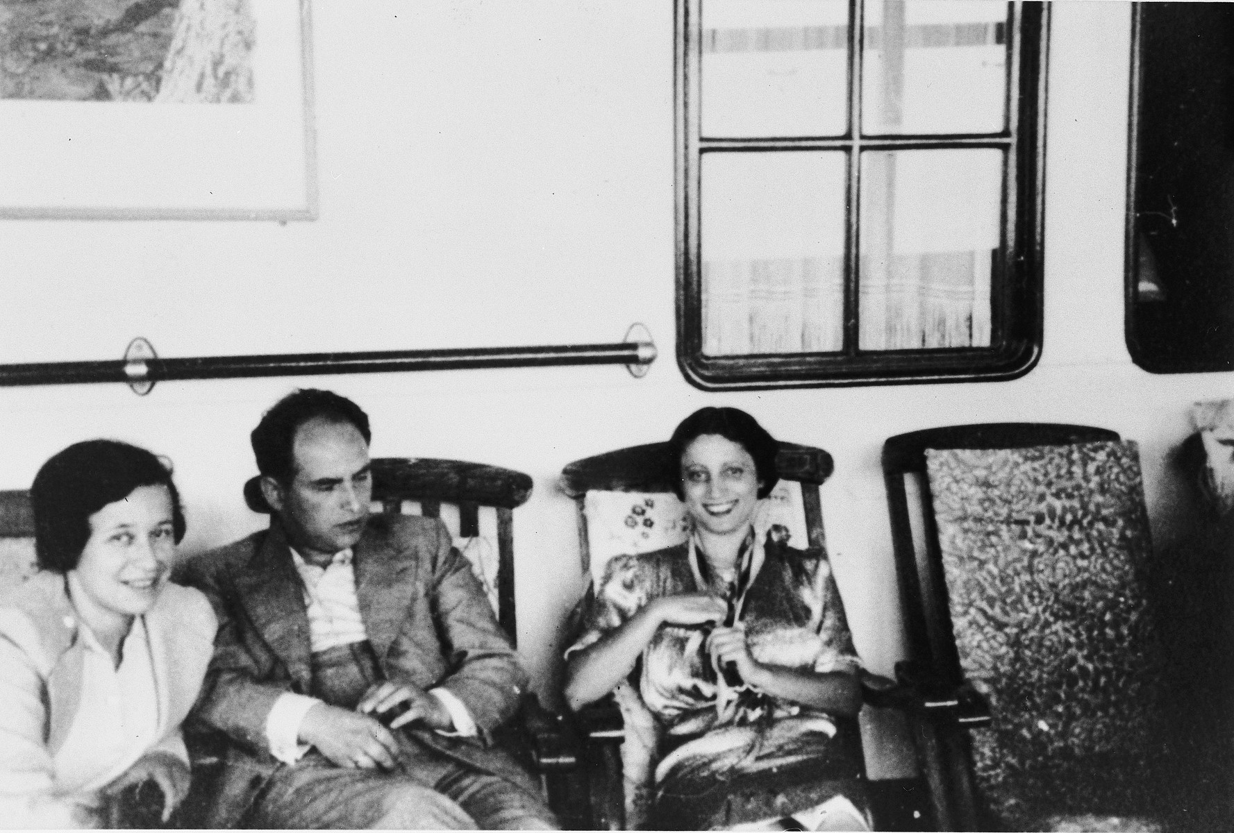 Three passengers relax on deck chairs on board the St. Louis.  From left to right are Irmgard and Josef Koeppel and Sofi Aron.
