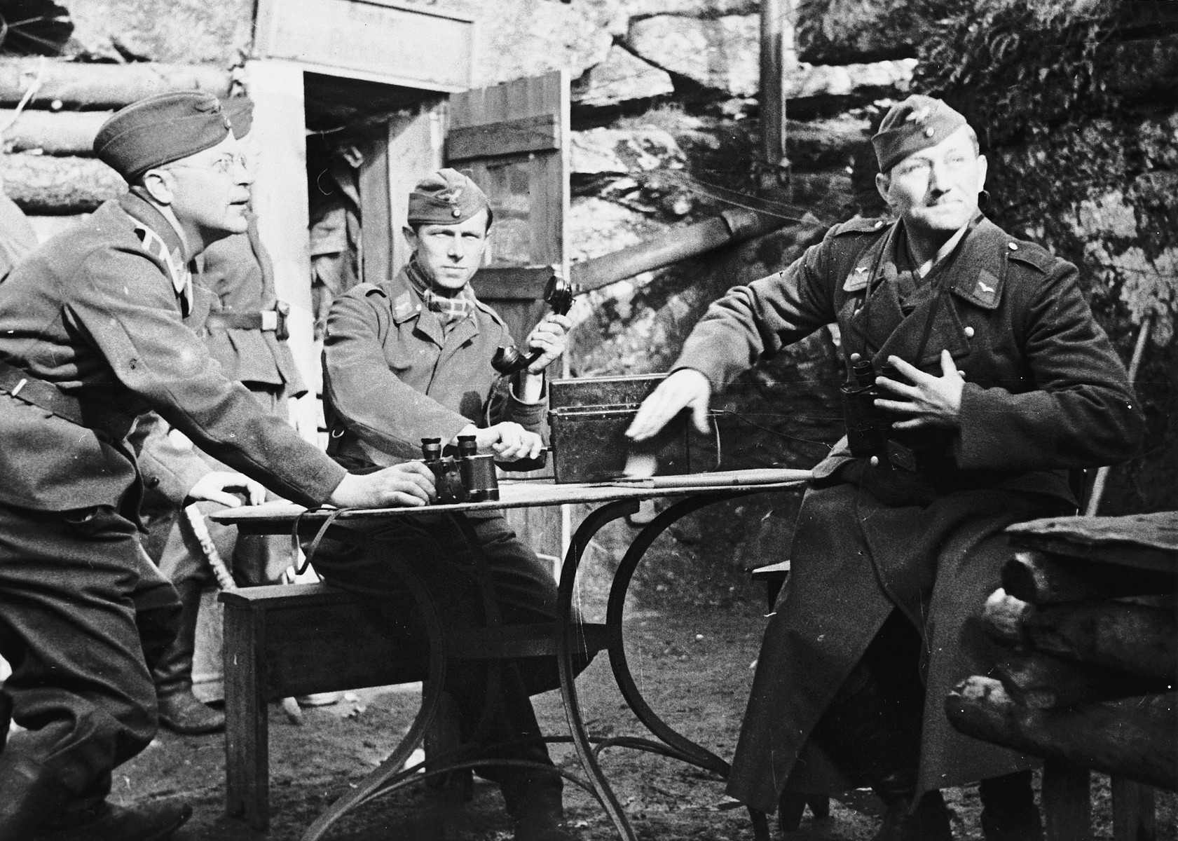 Three German soldiers sit outside a log house with their binoculors and radio in a makeshift command post [probably in the Soviet Union].