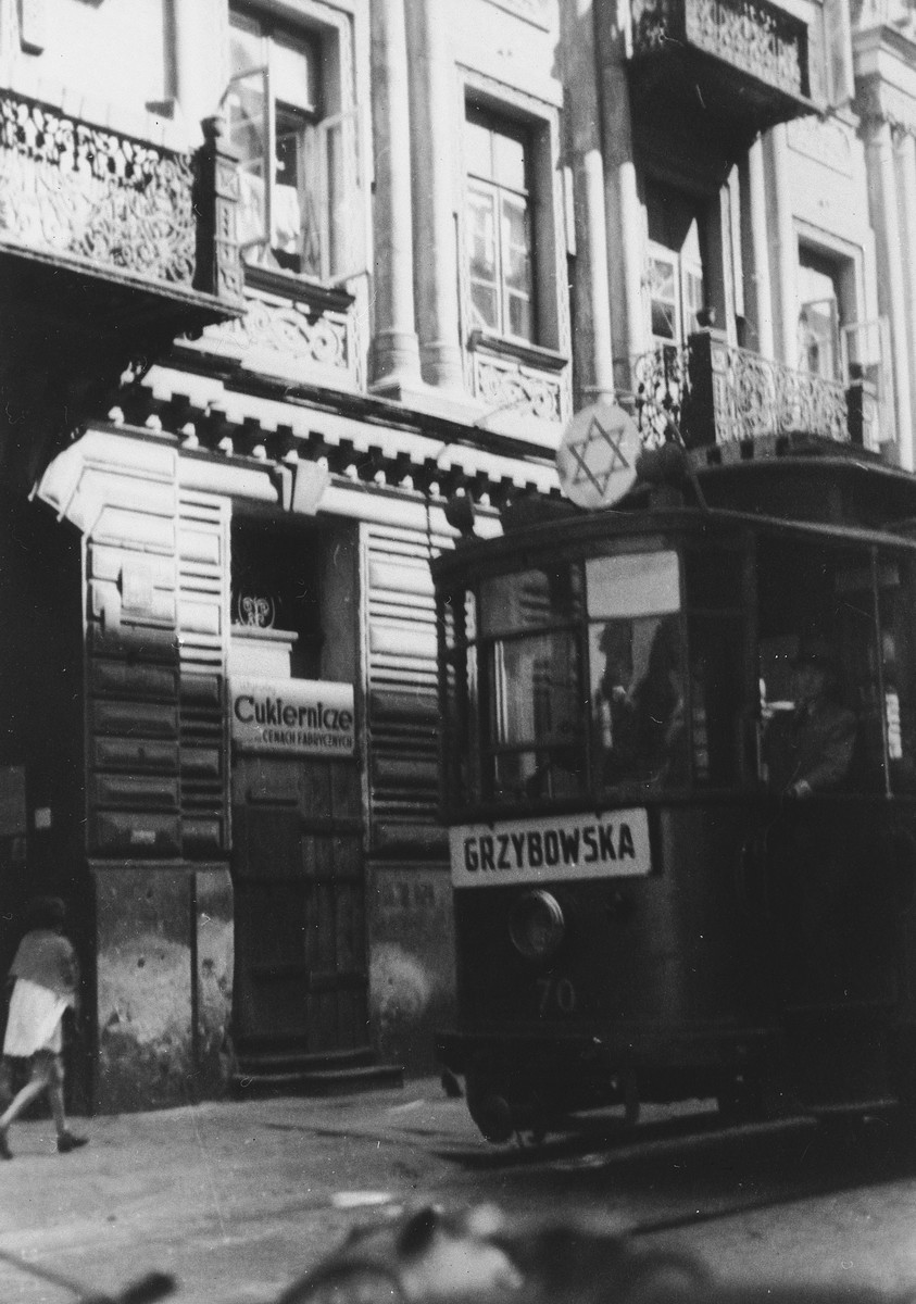 A streetcar marked with a large Star of David rides down a street in the Warsaw ghetto.  The sign on the front of the car says Grzybowska.