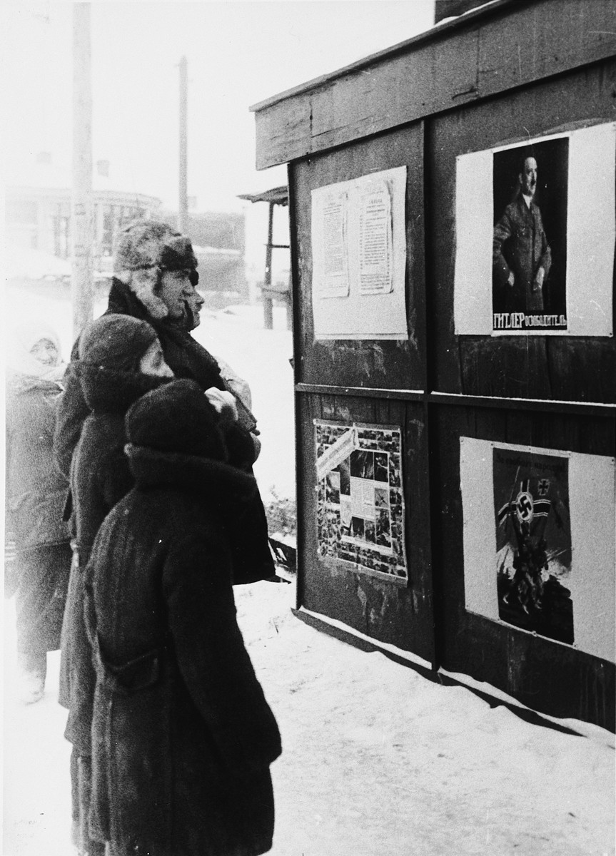 Soviet citizens examine Nazi propaganda tacked onto an outdoor bulletin board.
