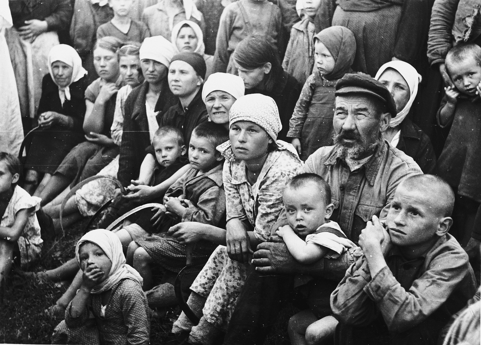 A large crowd composed mainly of Russian farmers. women and young children huddle together attentively on the ground in an unidentified location.