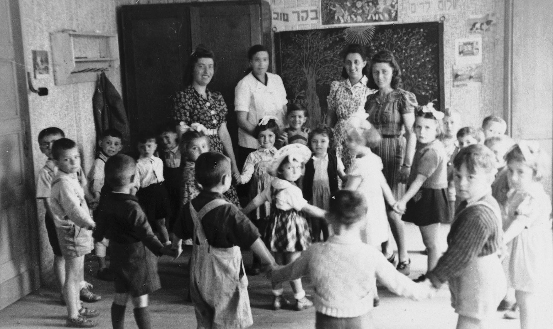 Preschool children dance in a circle in a classroom in the Wels DP camp.