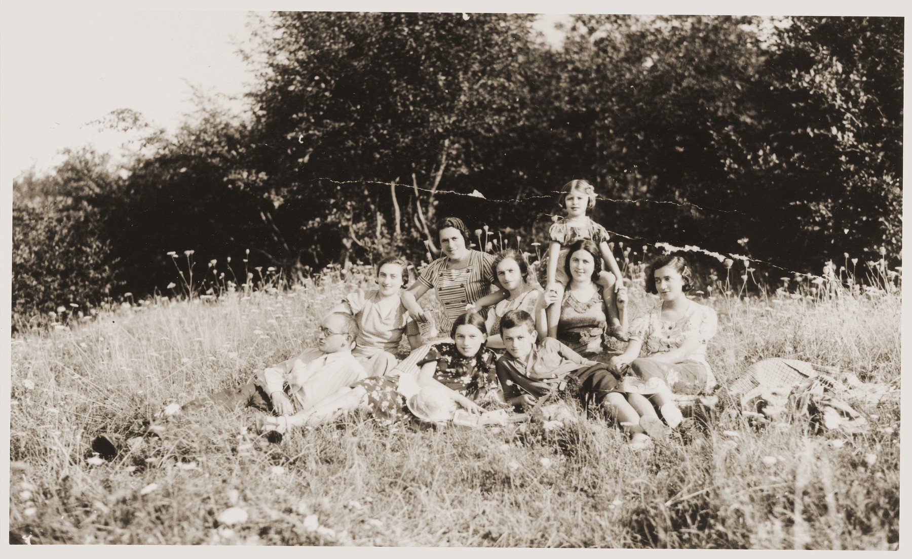 A group of friends picnics in the woods near Sadgura, Romania.  Included in the photo are Fritzi Brender, Perle Katz, Anna Rosenheck Brender, Bella Helenberg Nathan, Esther Hellenberg, Koka Reichman and David Katz.