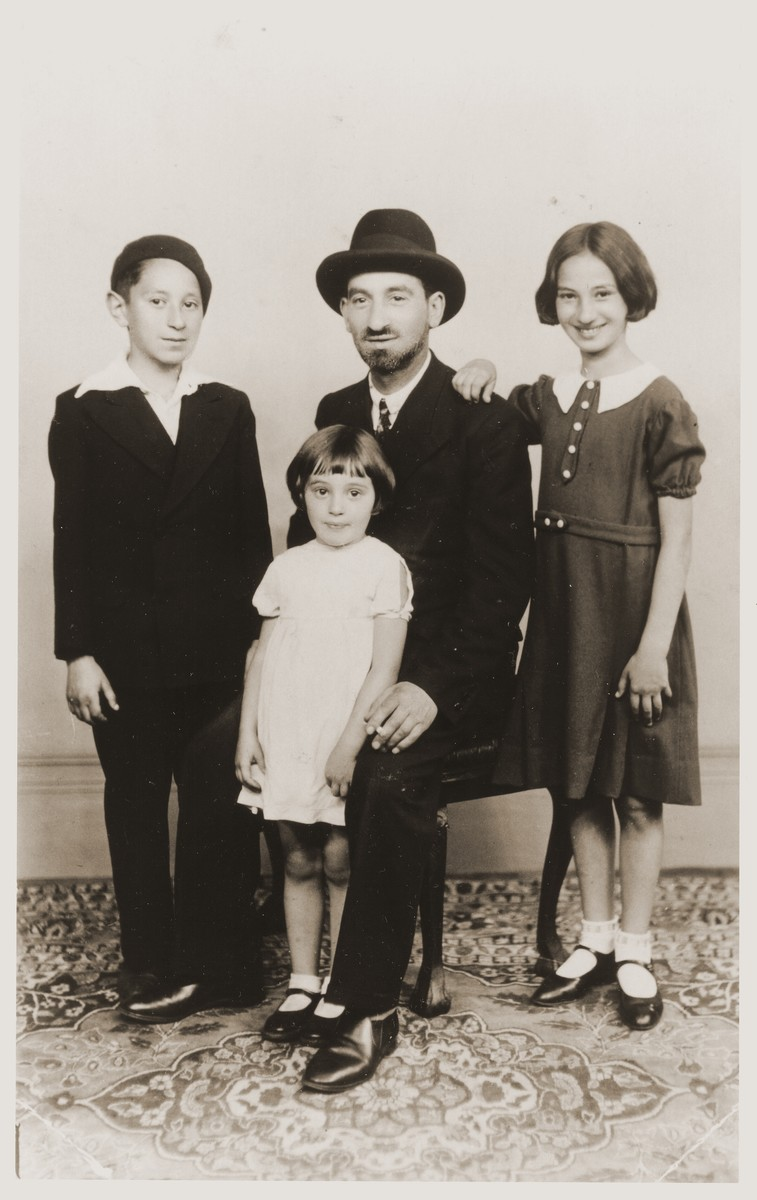 Studio portrait of a Jewish family in Brussels, Belgium.  Pictured are Zacharia Tuchsznajder with three of his children, Michael, Sarah, and Eva.