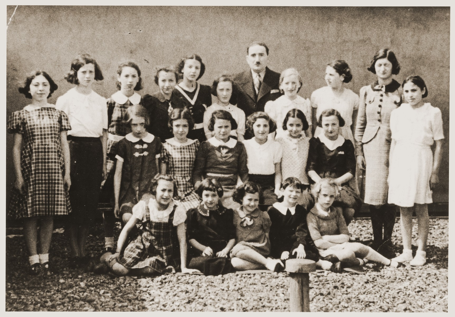 Group portrait of students and teachers from the Hebrew school at the Synagogue rue Clinique Anderlecht in Brussels, Belgium.  Among those pictured are Eva Tuchsznajder (front row, second from the left); Fanny Dickstein (second row, third from the left); Regina Grossman (back row, left); and Sarah Tuchsznajder (back row, third from the left).