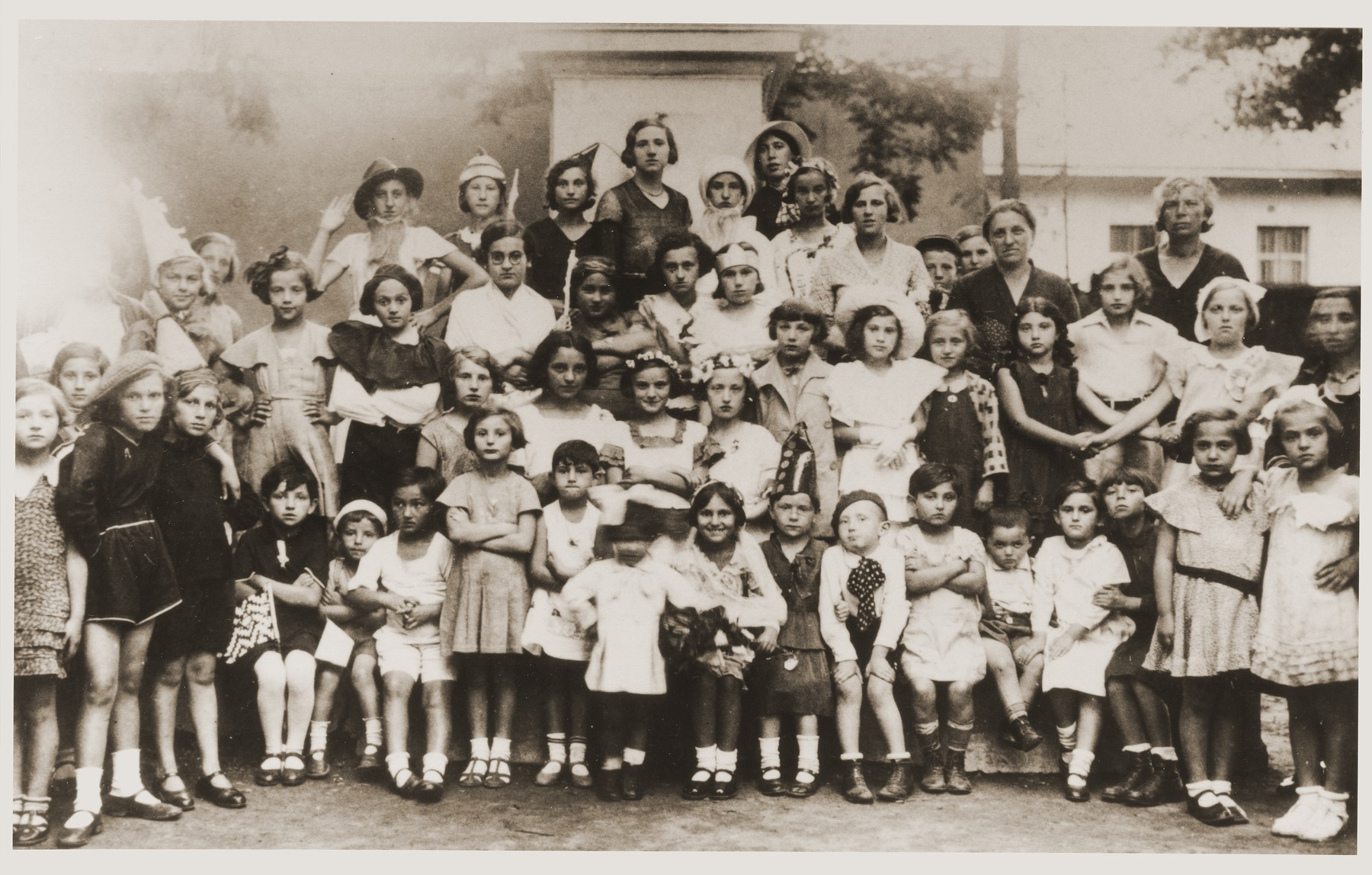 Group portrait of students in the Sadagura Beit Yaakov school dressed up in costumes to represent different Jewish holidays.  Included in the photo are Berta Weisberger (Purim), Heniu Reich (Sukkot), Schlioma Weisbach, Moli Korner (Yom Kippur), Fritzi Bender (Sabbath), Clara Lehr Kreisler, Sima Kerner, Paula Deresch Brunstein (Shavuot), Koko Kinsbruner Laor and Rabbi Landau's two children.