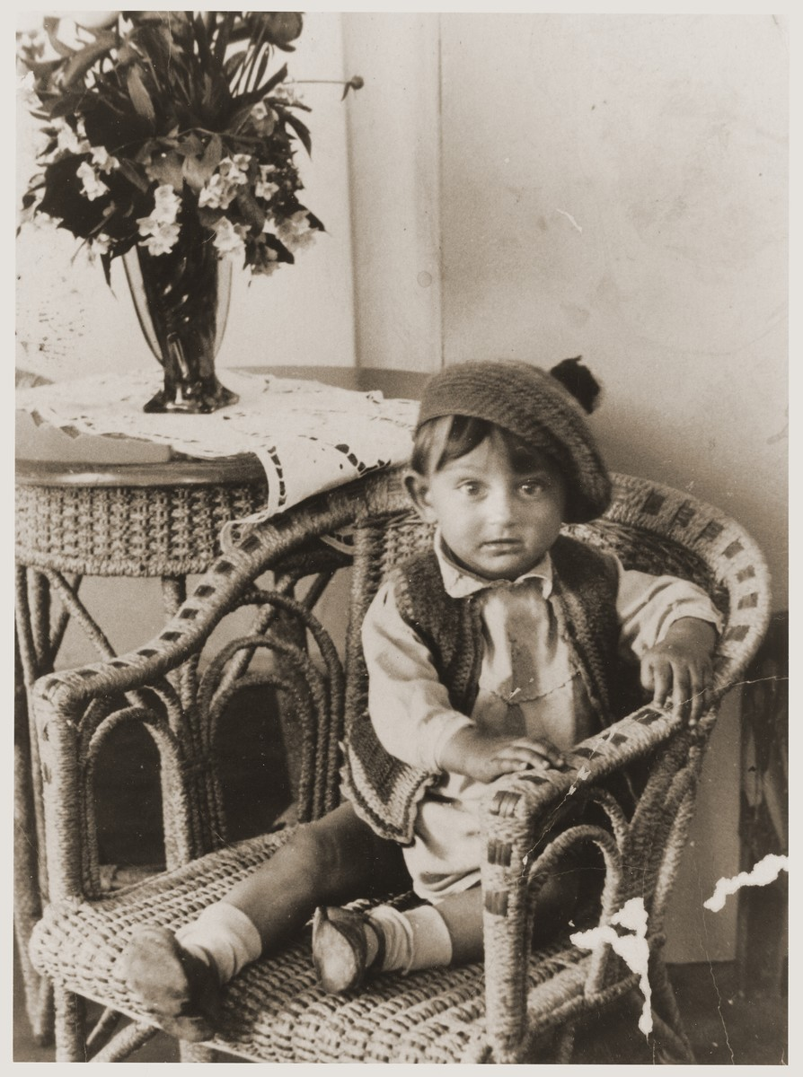 A young Jewish boy wearing a tam sits in a chair at his home in Kazimierz.  The child, who was a cousin of Eva Tuchsznajder, perished during the war.
