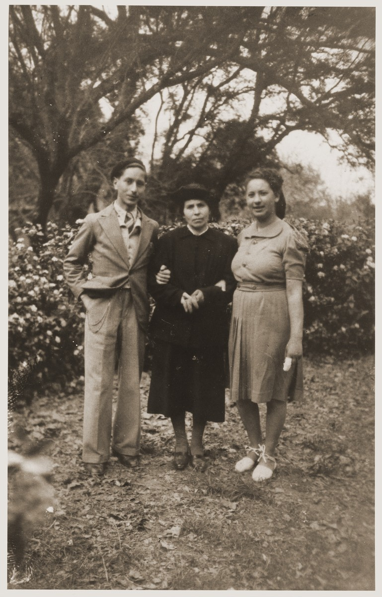 Esther Erlich Tuchsznajder poses with her children, Michael and Sarah in a park.  This photograph was the last one taken before their deportation to Auschwitz.
