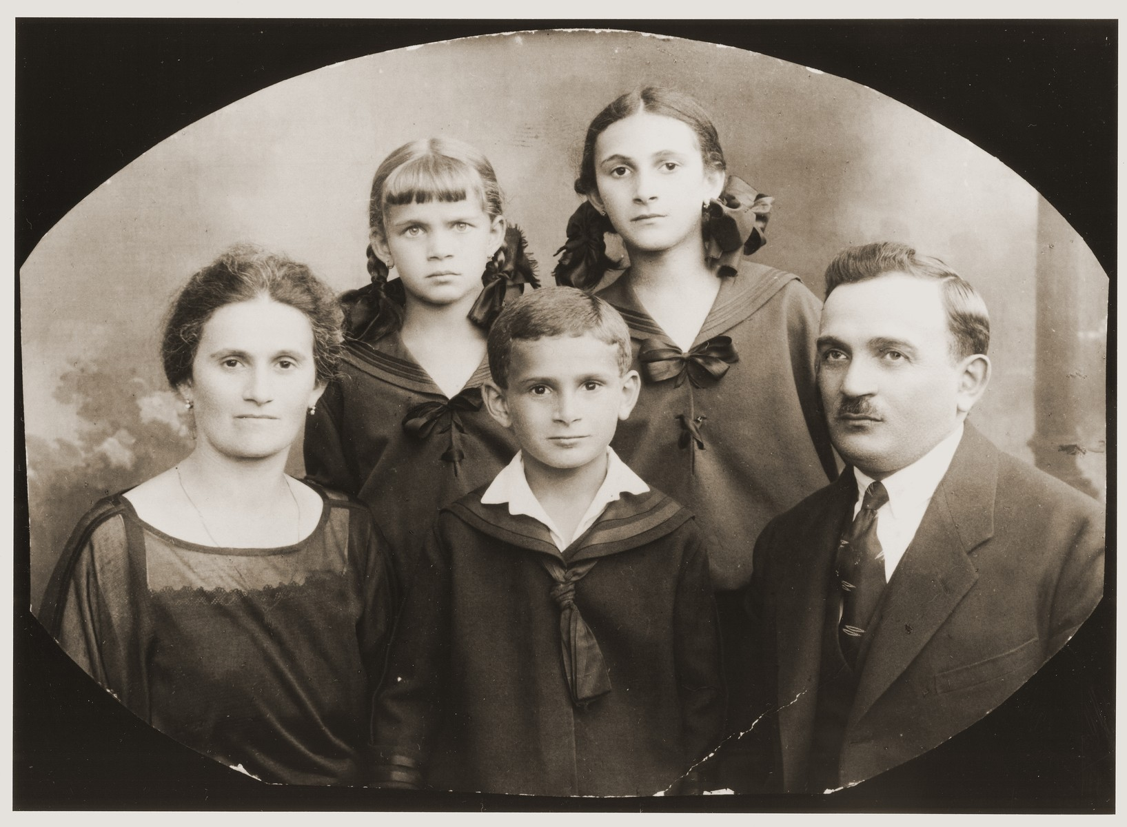 Studio portrait of the Senenseib family, all of whom later perished in Auschwitz.  Pictured from left to right are: Regina Rosenheck Senenseib, Clarzia Senenseib, Mundic Senenseib, Fridka Senenseib, and Abraham Senenseib.  The Senenseib family were relatives of the donor, Frieda Brender.