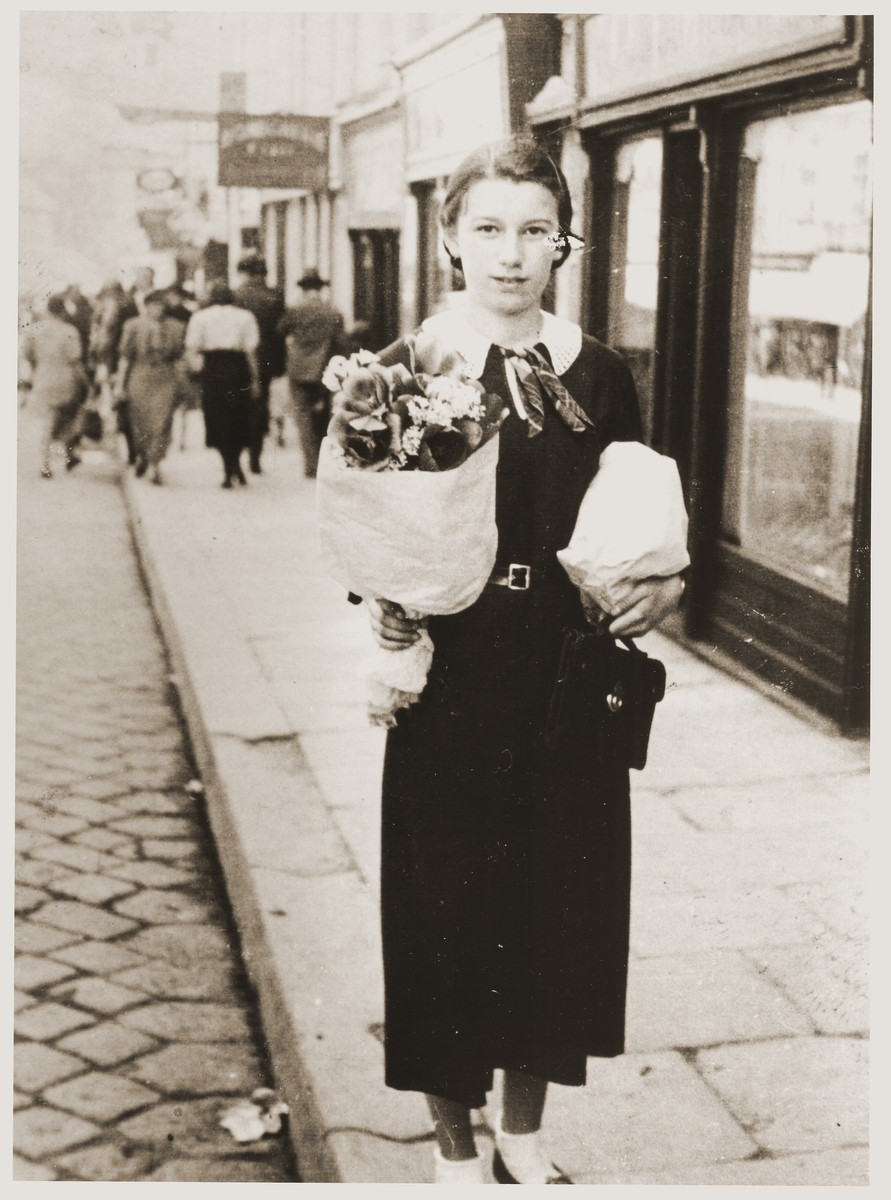 Fritzi Brender carrying flowers for her teacher on a street in Cernauti.
