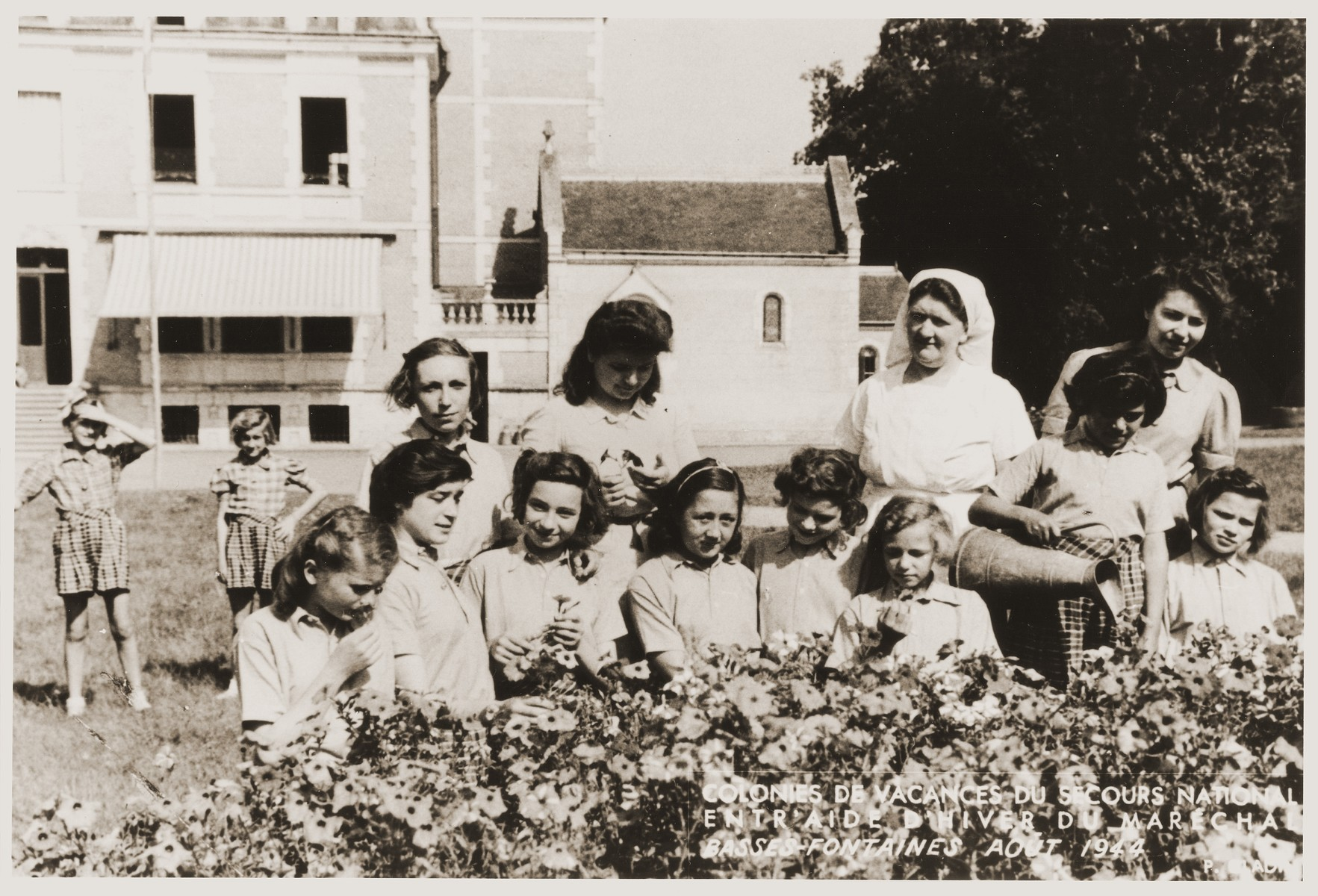 Group portrait of girls in the garden of the Les Basses-Fontaines children's home, where Jewish children were hidden during the war.    Among those pictured (with their aliases) are Eva Tuchsznajder (Yvonne Drapier) and France Cohen (Colin).  The caption identifies Les Basses-Fontaines as a vacation home sponsored by Petain.