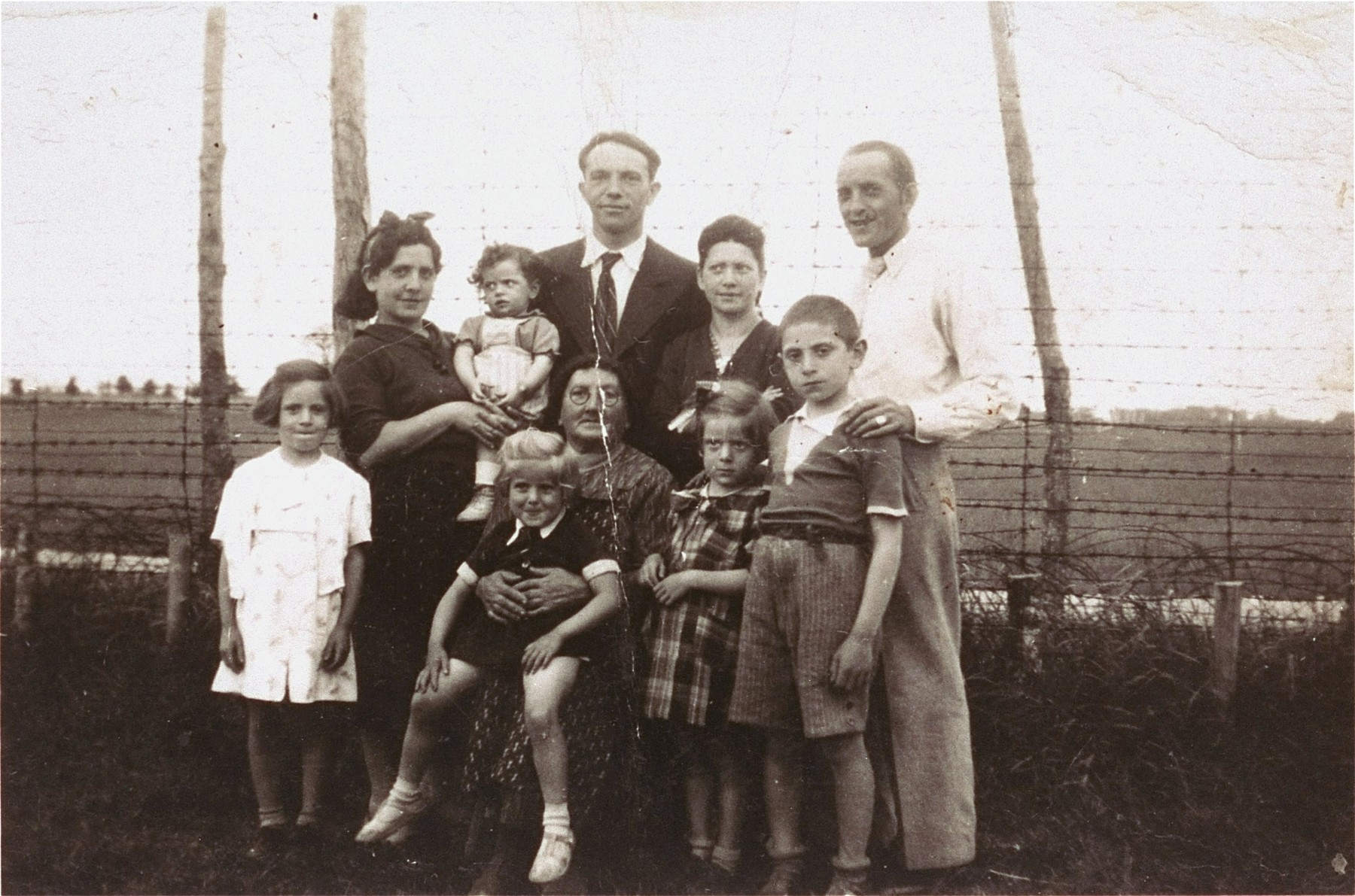 Members of the Goldstein family pose with Nechemia and Esther Kluger in the Poitiers internment camp.    Pictured from left to right are: Anna Goldstein (10), Faigle Goldstein (35), Nechemia Kluger (43), Esther Kluger (40), Llata Goldstein with Renee Goldstein (7), Lara Goldstein (5), David Goldstein (13), and Albert Goldstein (34).