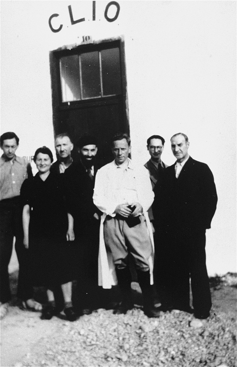 Members of CLIO (Le Comite d'liaison israelite du oeuvres), the Jewish liaison committee who helped implement the medical and social assistance programs of the OSE relief agency in the Rivesaltes transit camp.  Pictured third from left is Erwin Heilbronner.  Also pictured in the center is Rabbi Jacob Bloch, the founder and chair of the committee and rabbi of the camp. Dr. Malkin of the OSE is pictured in the white coat.
