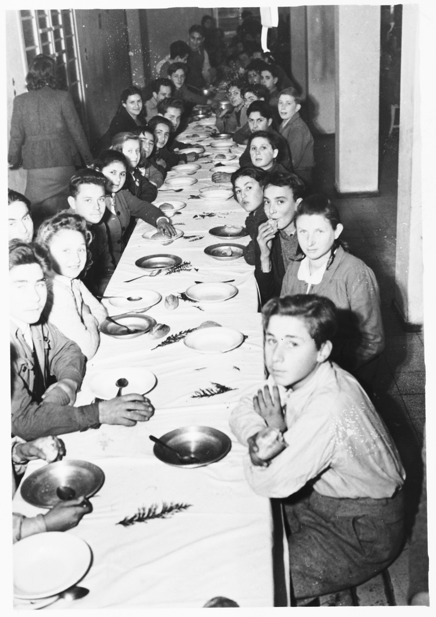 Jewish youth gather around a table to celebrate the Sabbath in the dining room of the Youth Aliyah children's home in Selvino, Italy.  Among those pictured are Mania Bander, Esther Werber and Zipora Kutner.