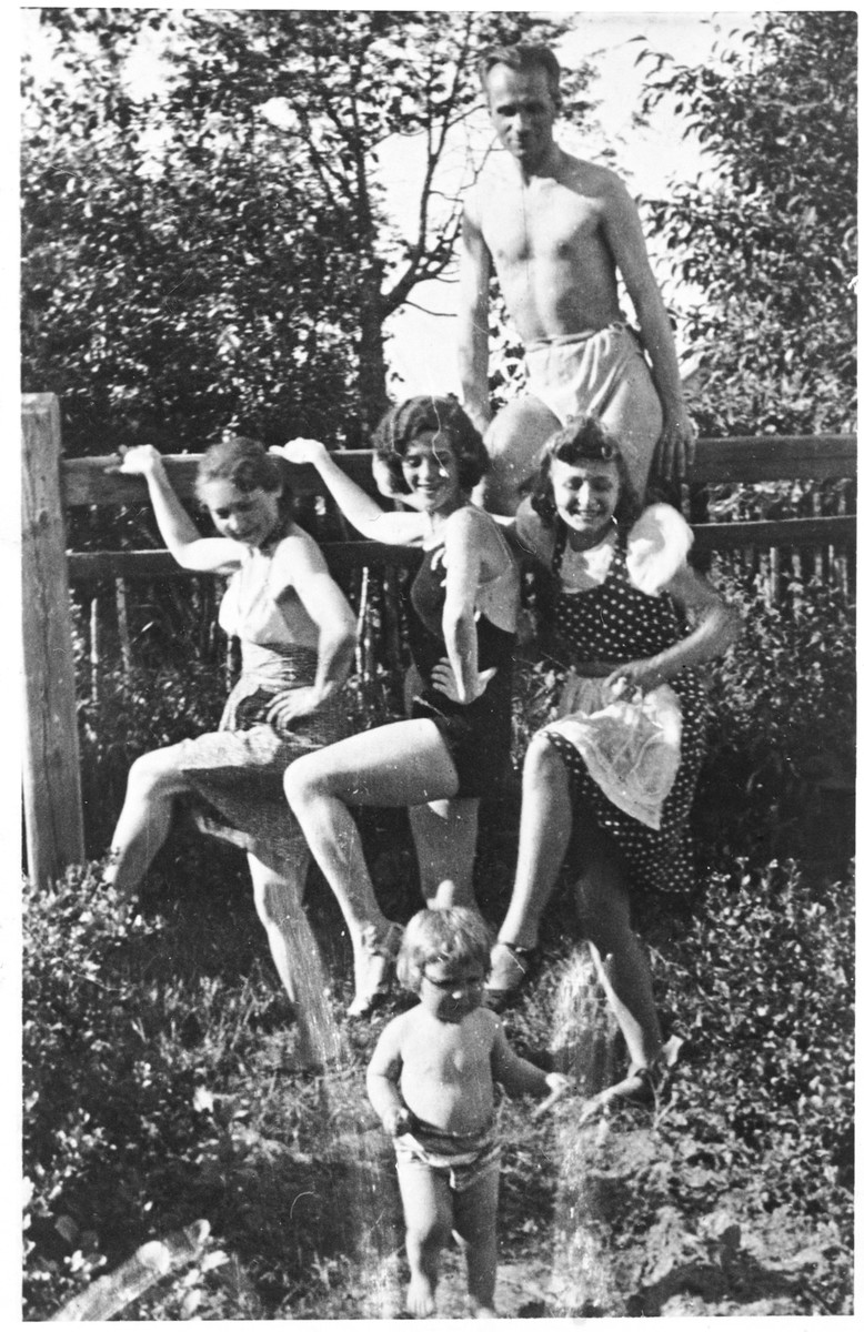 Dorota  Reichman relaxes in a garden with Polish friends while in hiding in Zimna Woda.    Her daughter Zofia stands in the front.  The women from left to right are Dorota, Ewa Donikowska and Marysia Hupert.  Tadeusz Witwicki is in the back.
