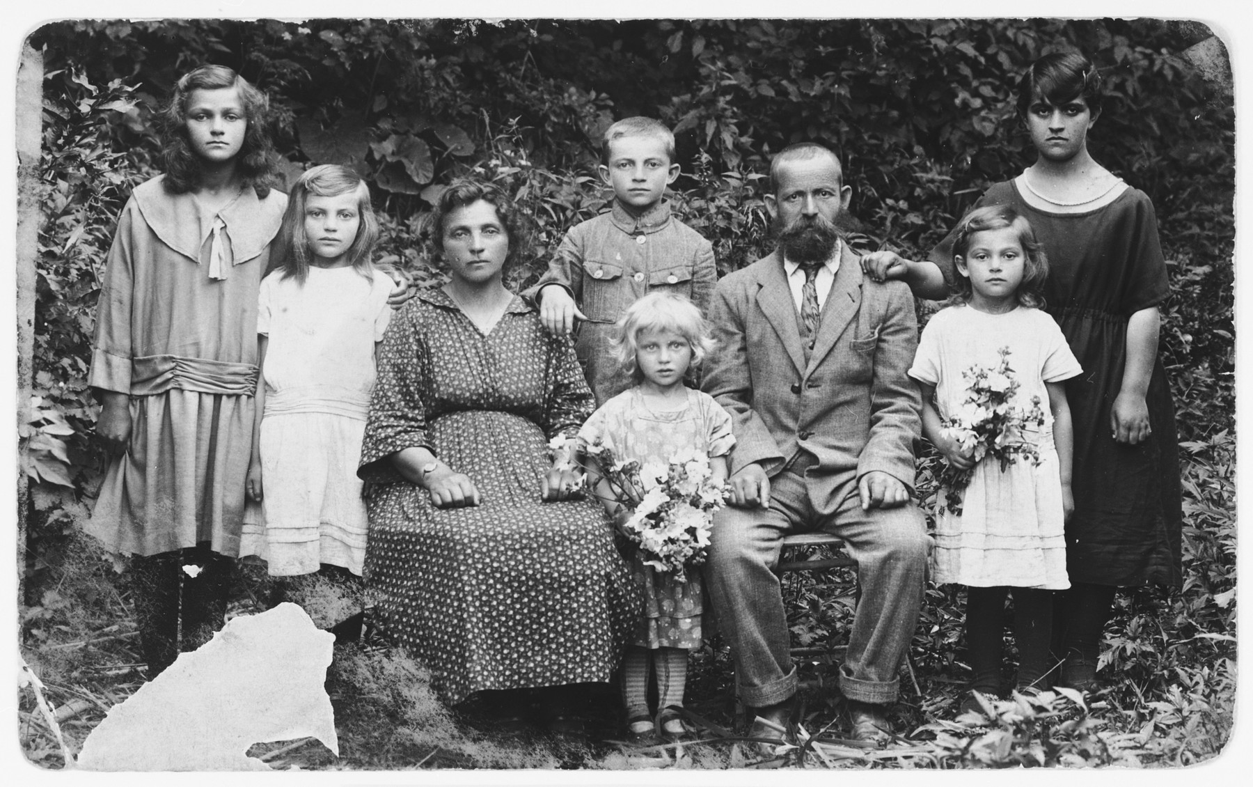 Mordechai and Sheindel Rajs pose outdoors with their six children.