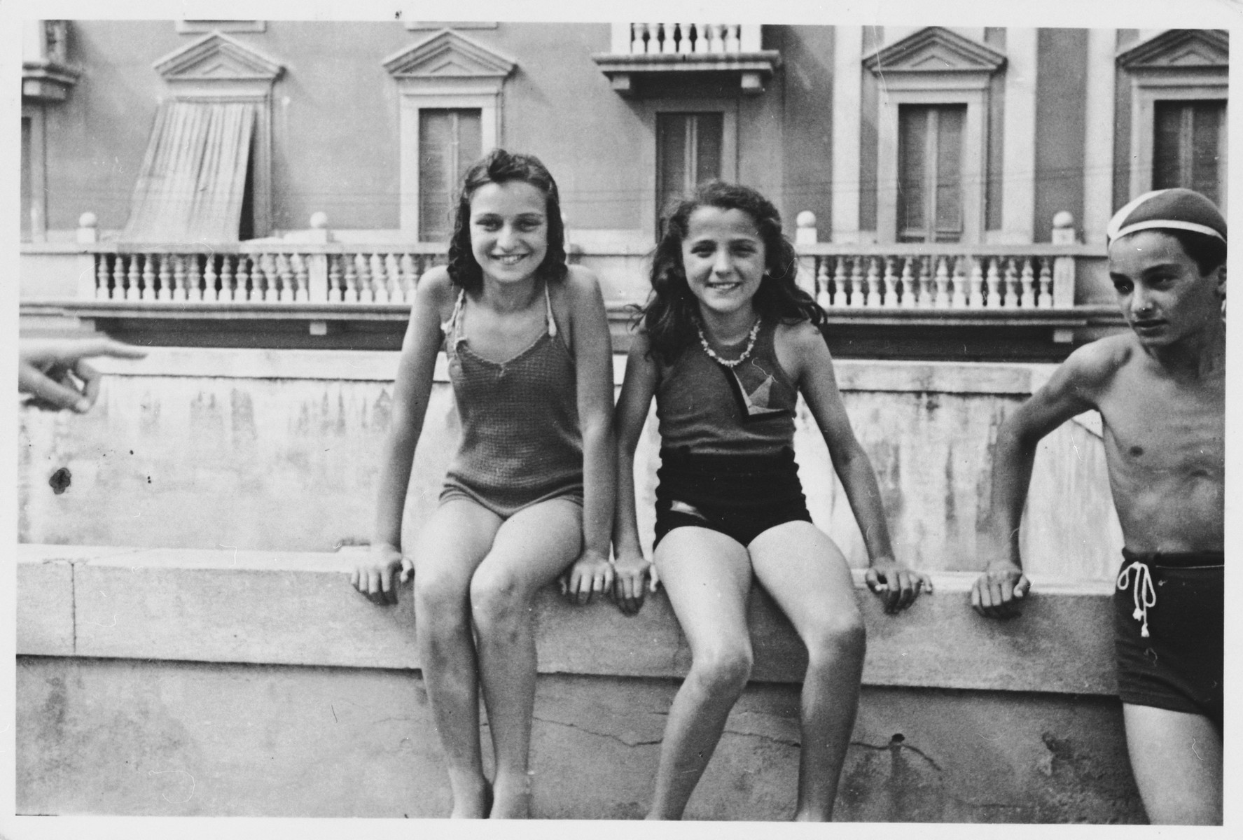 Mia Kaufman (right) poses sitting on a wall with a friend.