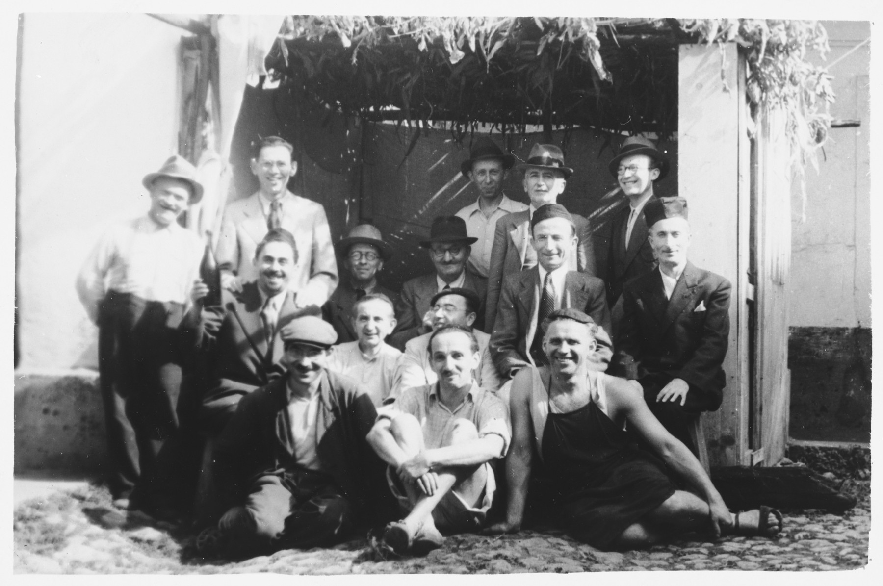 Jewish prisoners in a labor camp in Salerno, Italy pose in a sukkah.  Josef Kaufman is pictured in the middle row, second from the right.