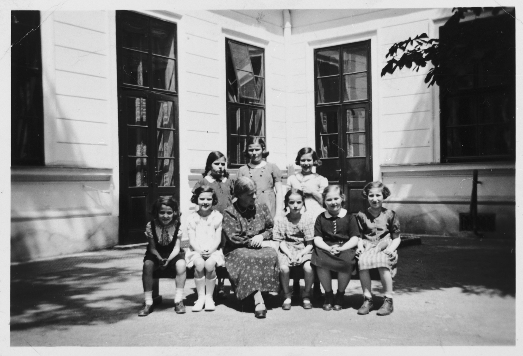 Jewish school girls pose for a class portrait with their teacher in Vienna.  Pictured on the left is Mia Kaufman.